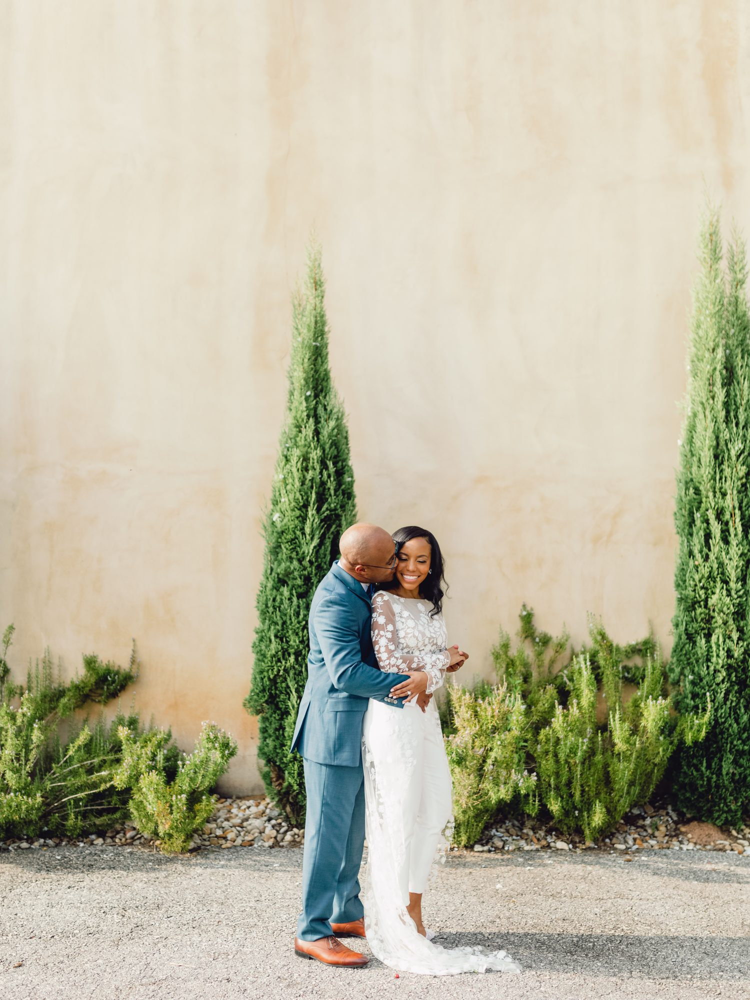 cayla david wedding couple smile and hug surrounded by shrubs and greenery