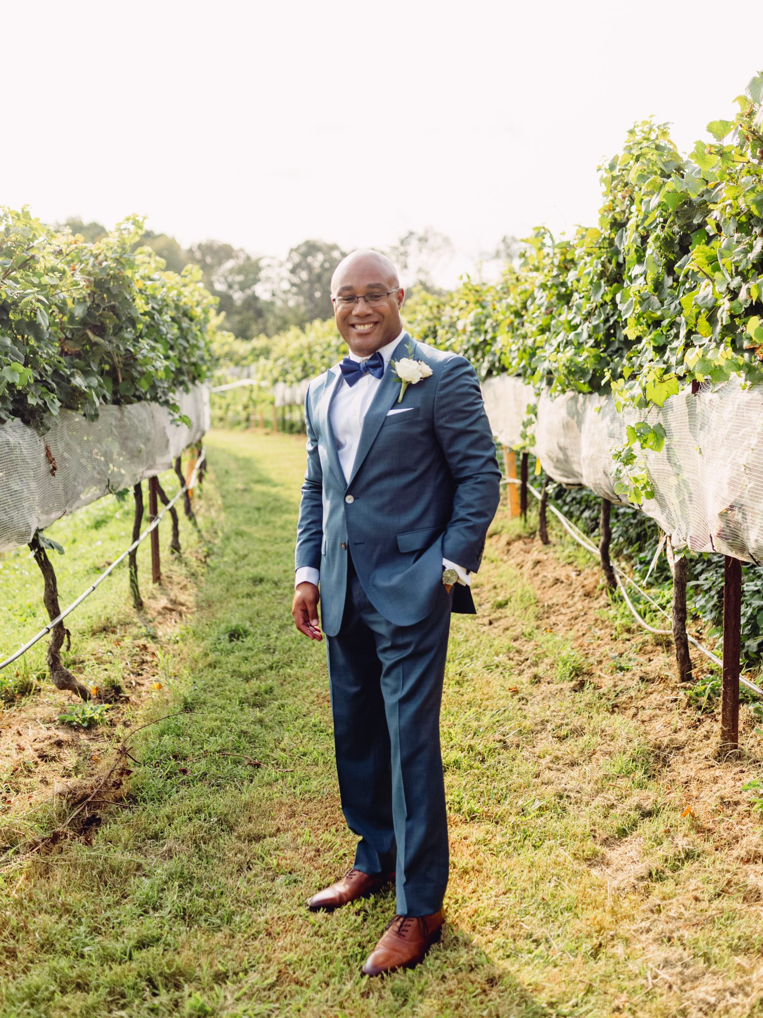 cayla david wedding groom posing in navy-blue suit at the winery venue