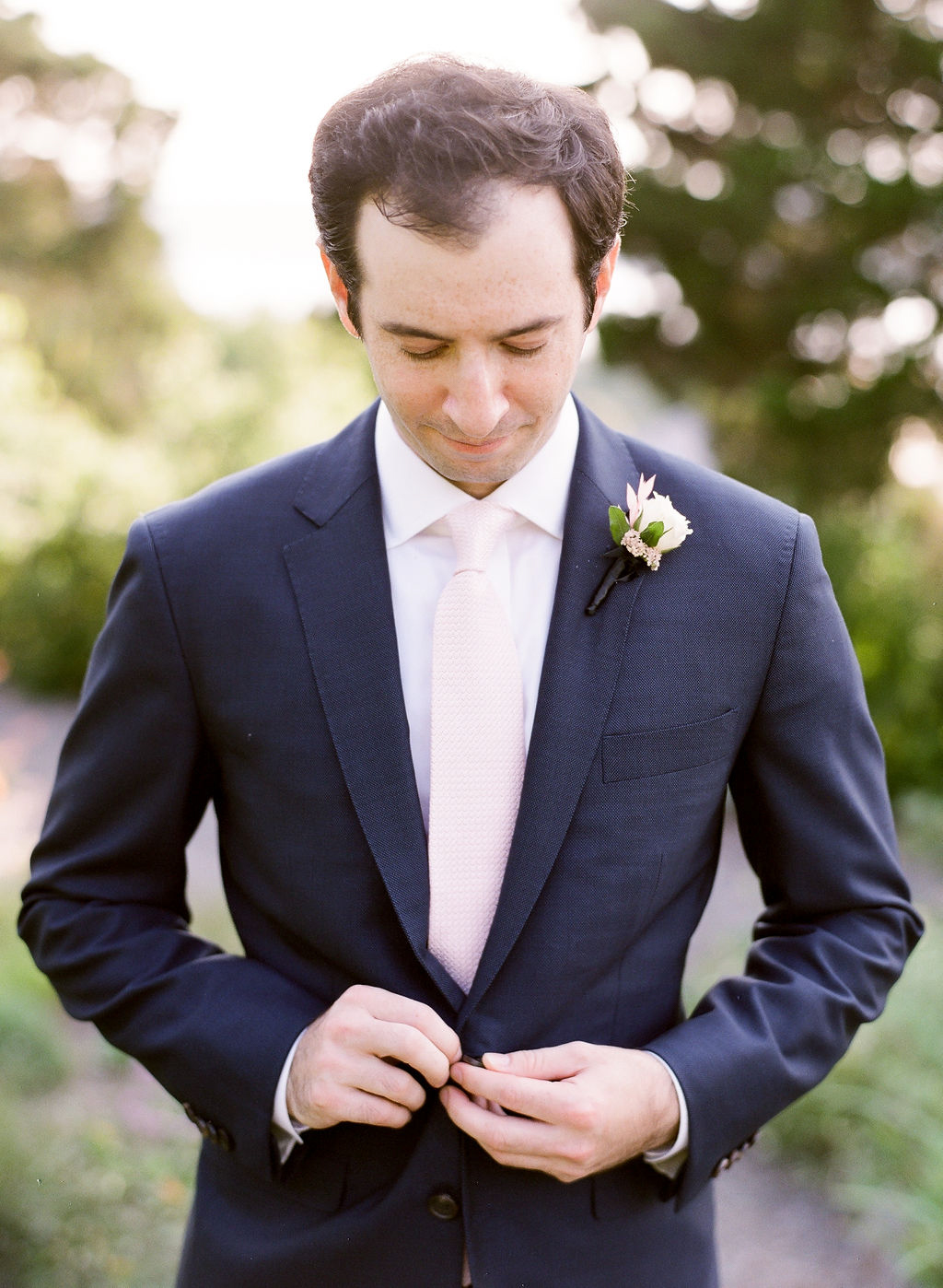 groom buttoning wedding suit jacket
