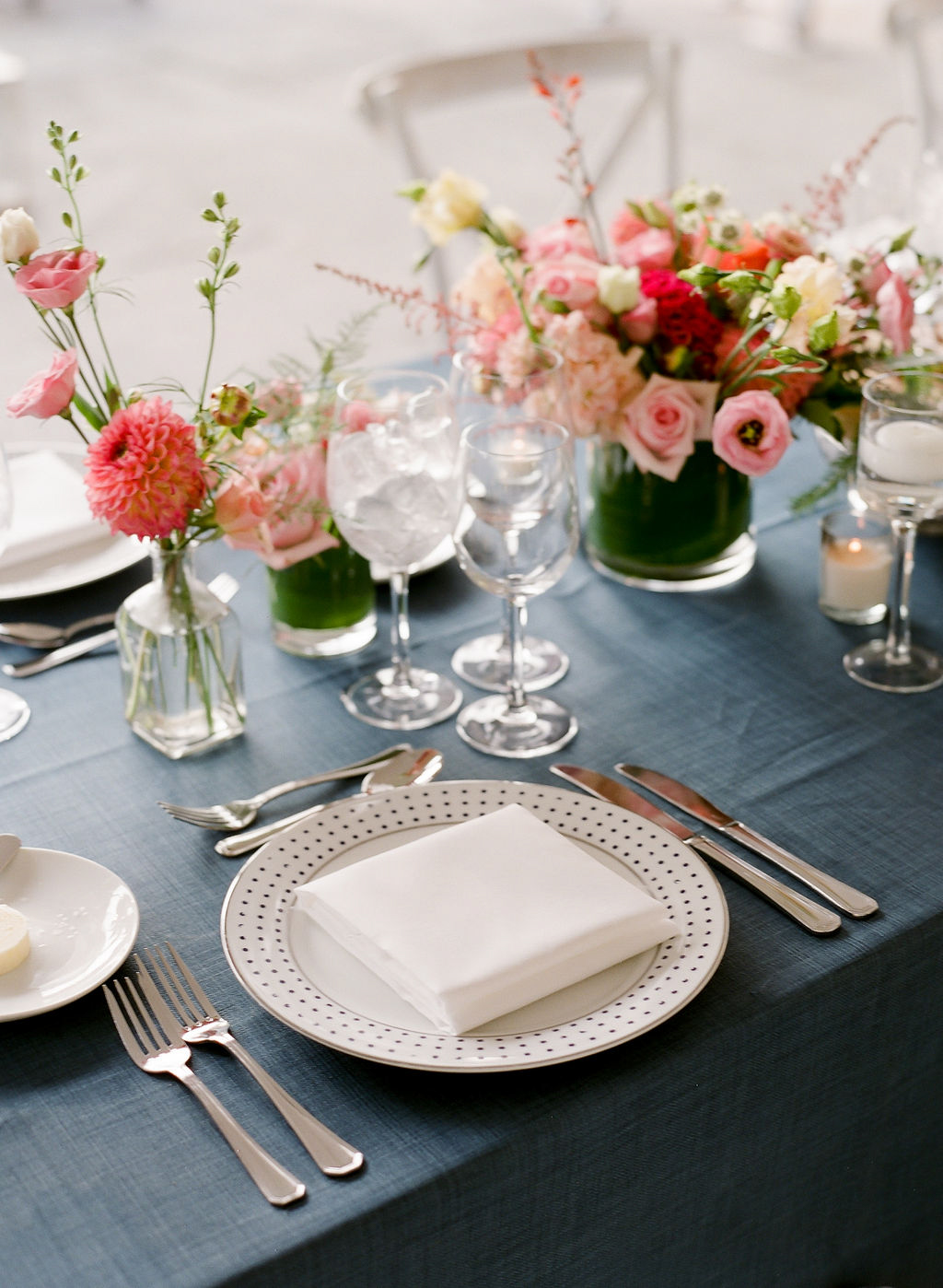 elegant wedding reception place setting with blue tablecloth and pink flowers