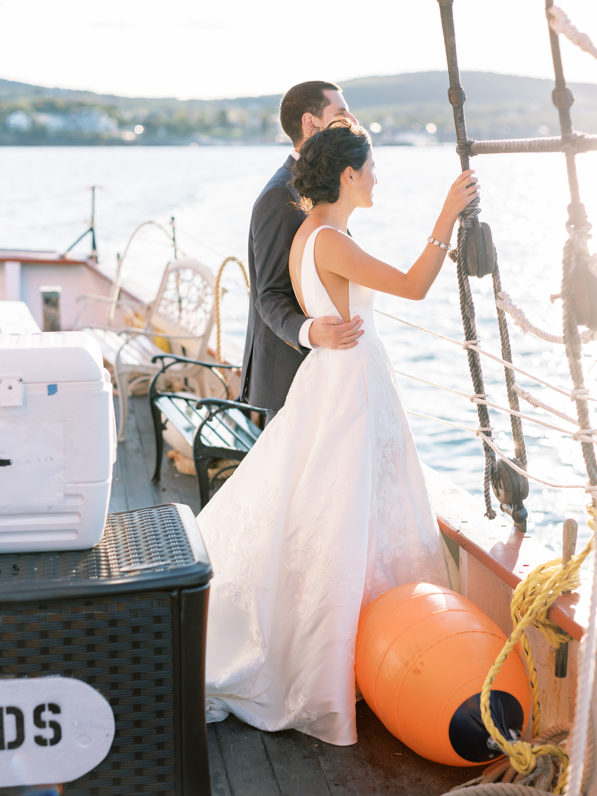 bride and groom looking into the sun on a boat