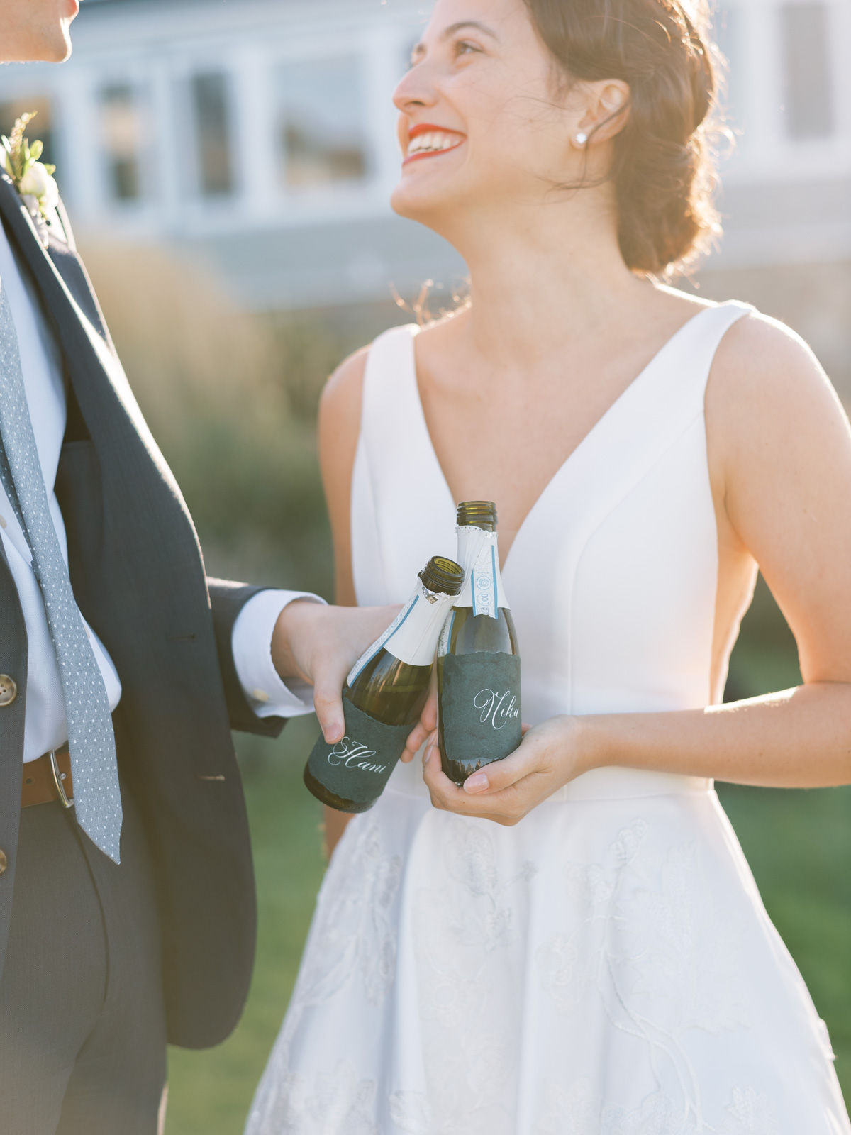 bride smiling at groom holding personal sized champagne bottles