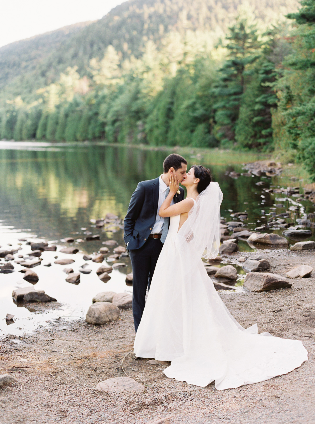 bride and groom kissing on sandy shore line