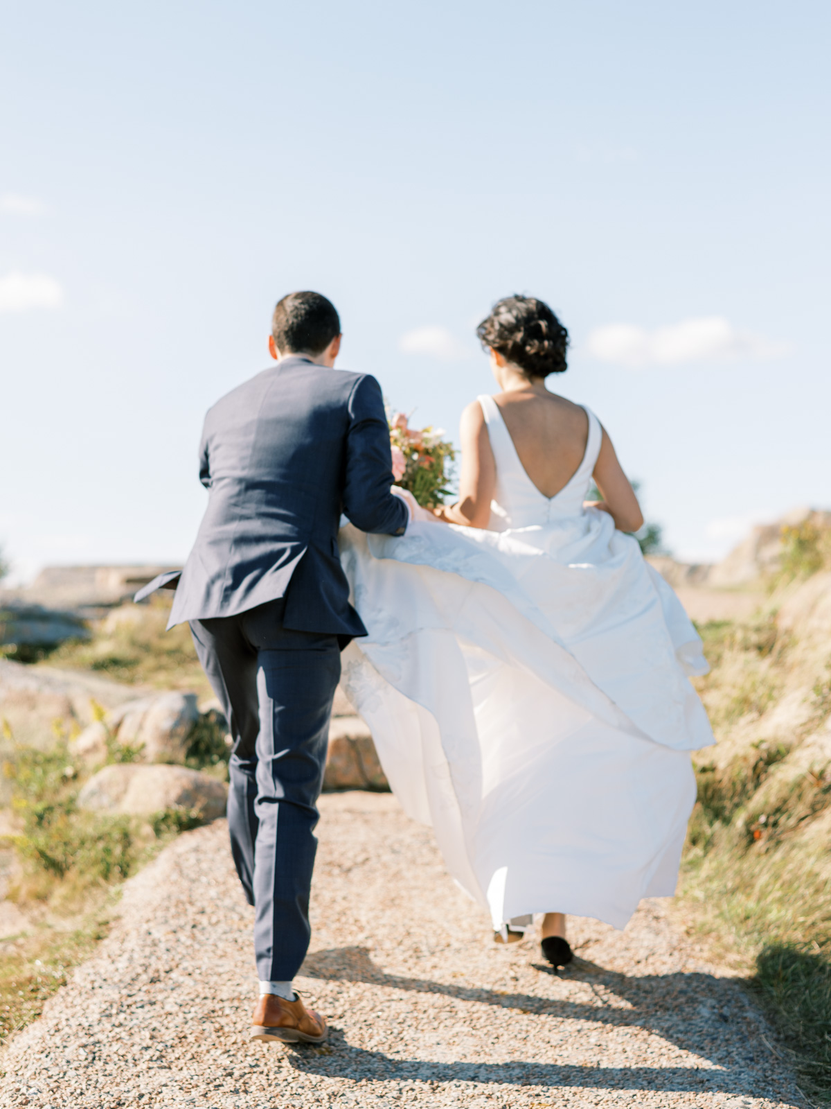 groom holding up brides dress as they walk away on rocky path