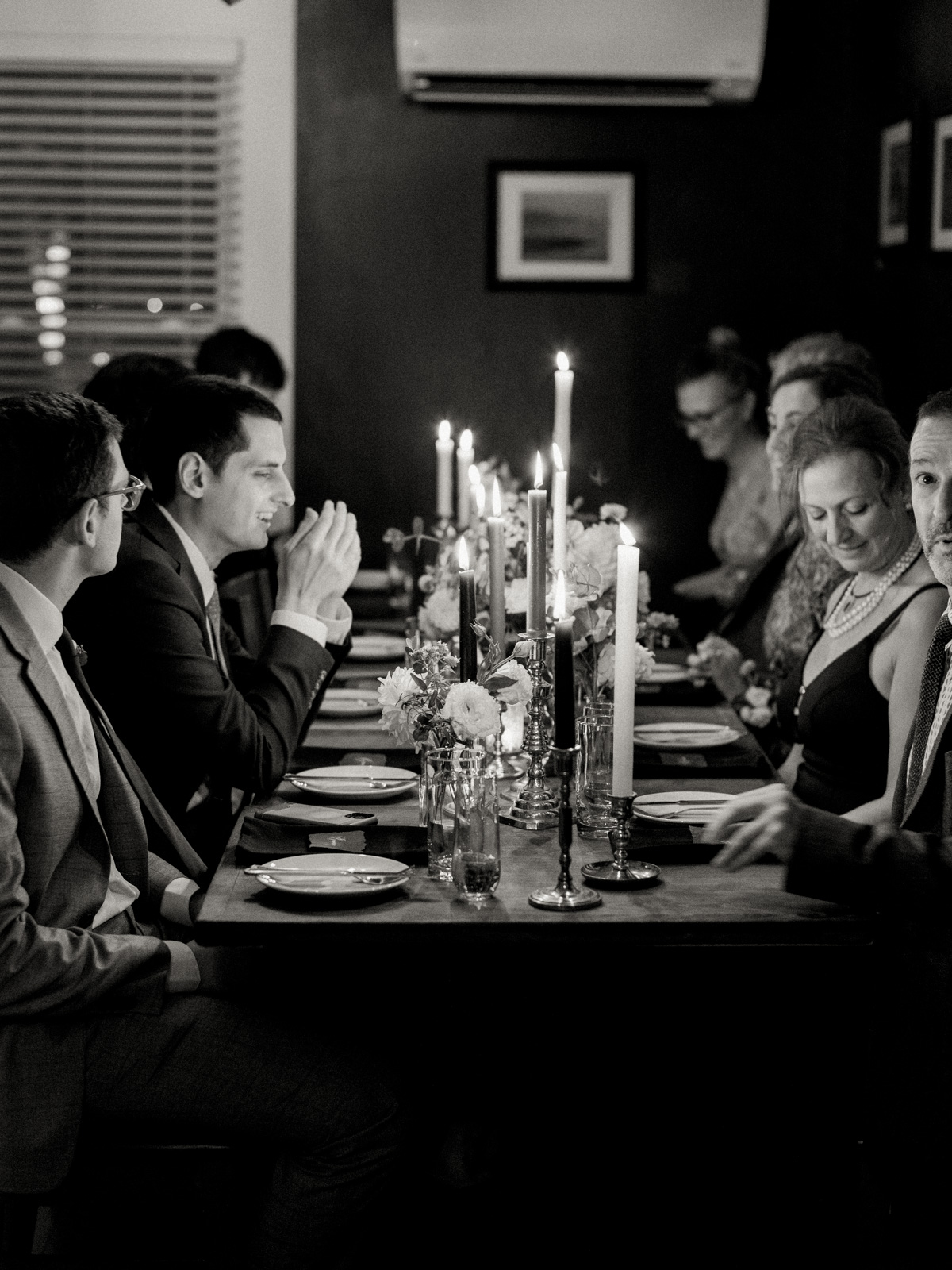 bride and groom family seated at candle lit table