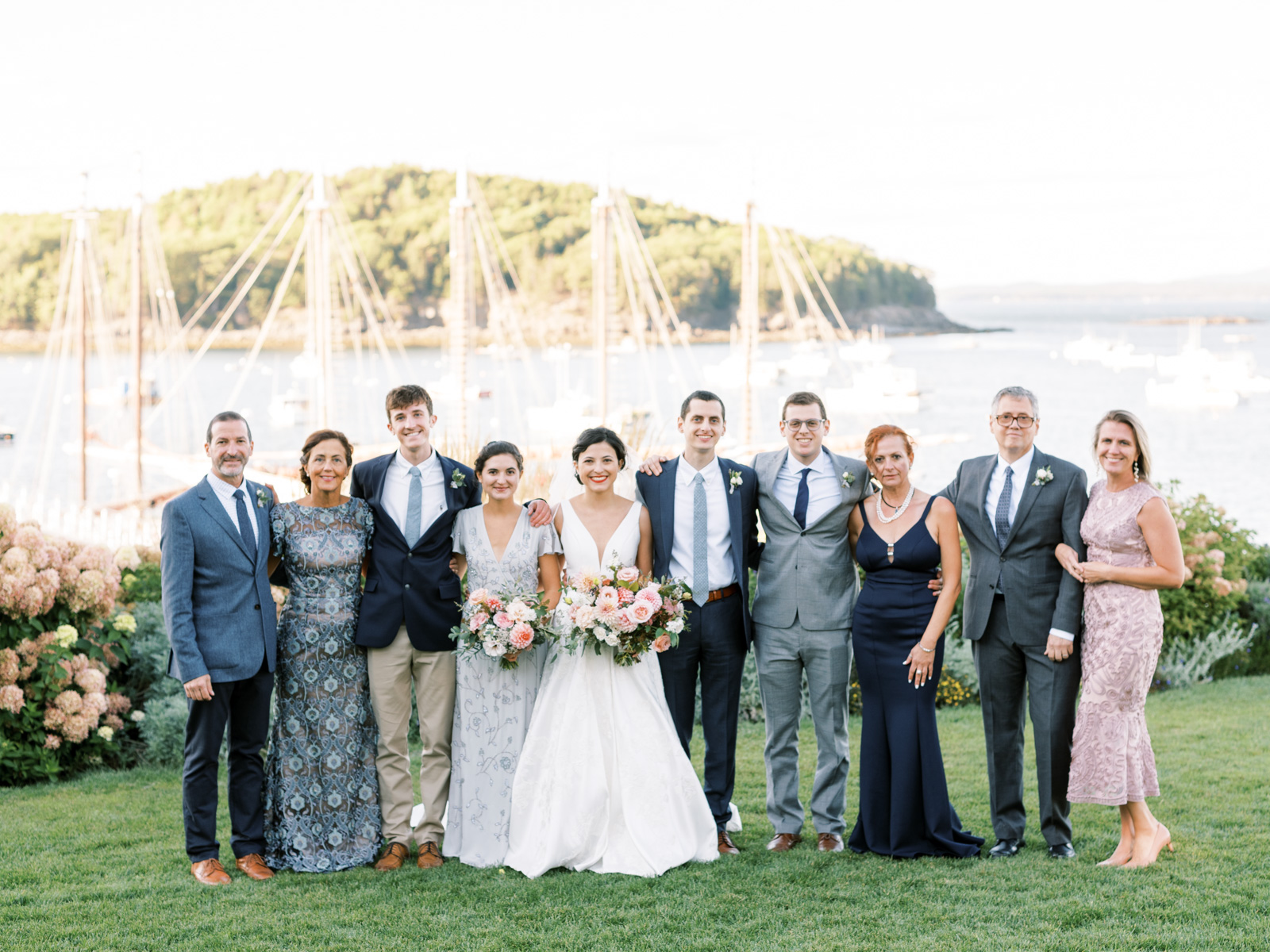 bride and groom smiling with their family for portrait shot outside