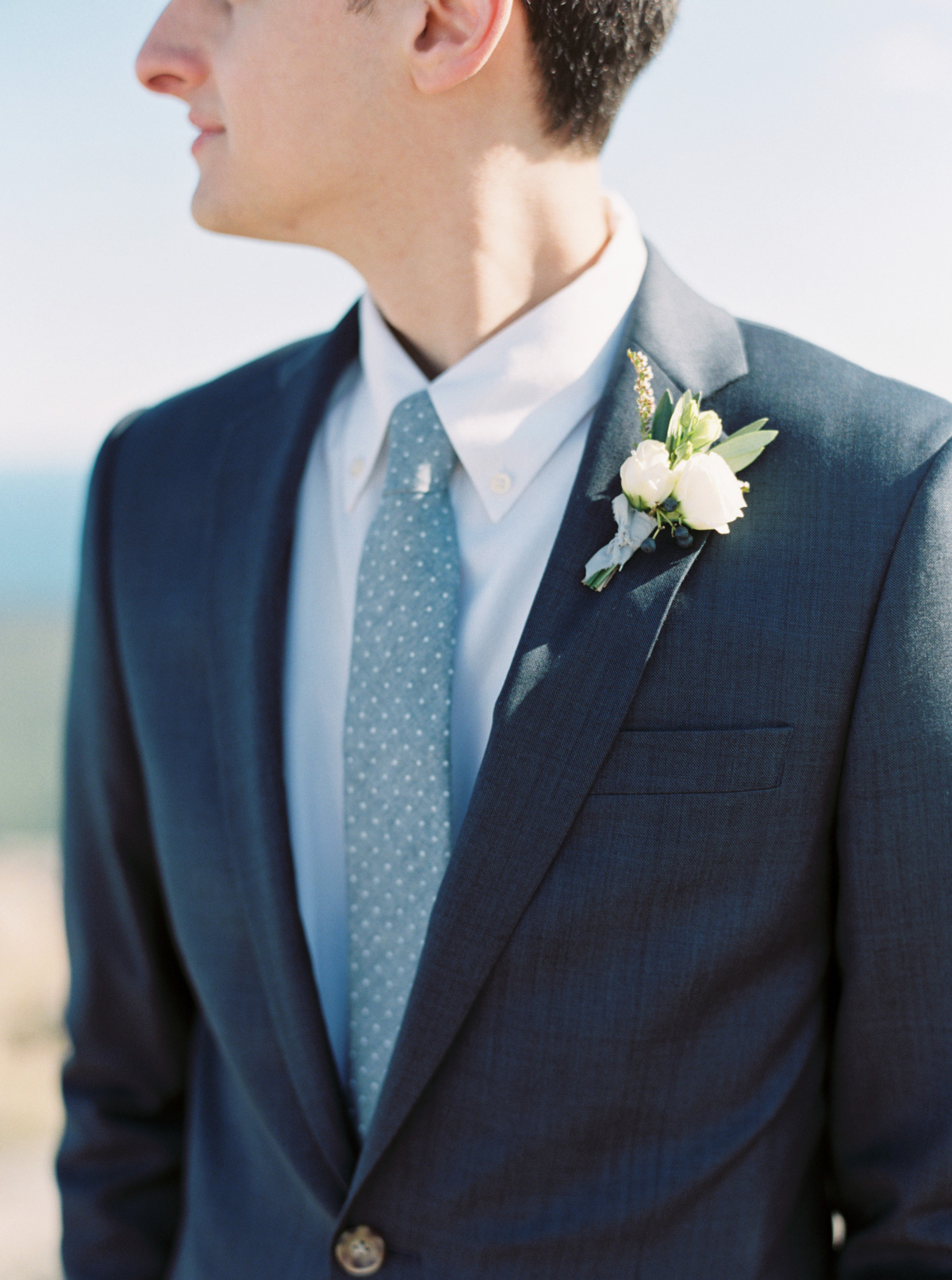 groom wearing navy suit with spotted blue tie