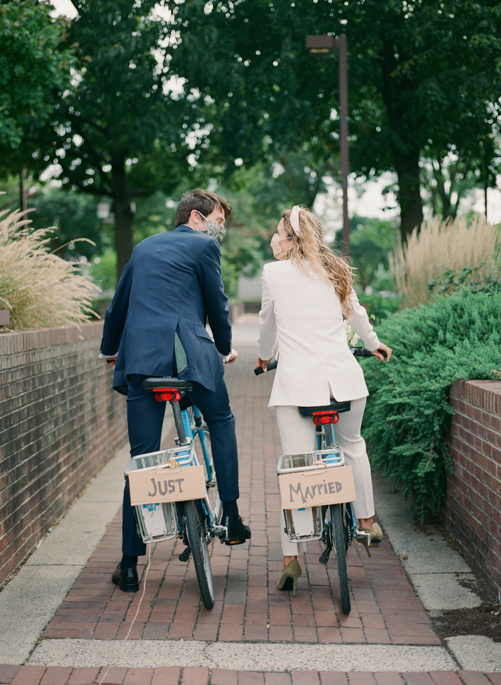 couple in black and white suits on wedding bikes