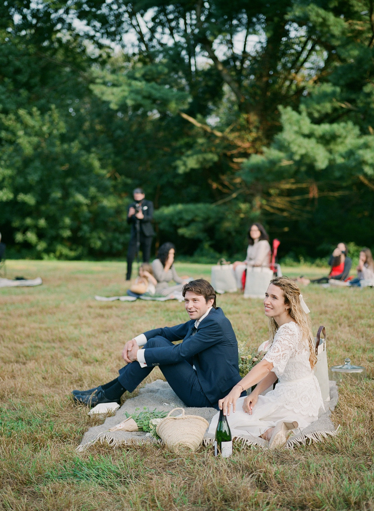 bride and groom seated on blanket for reception picnic