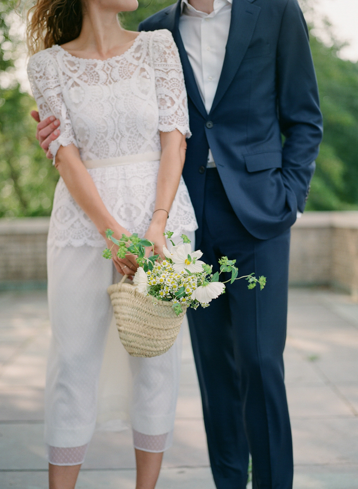 bride and groom with wedding bouquet in basket