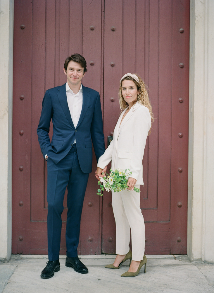 wedding couple in front of red door portrait