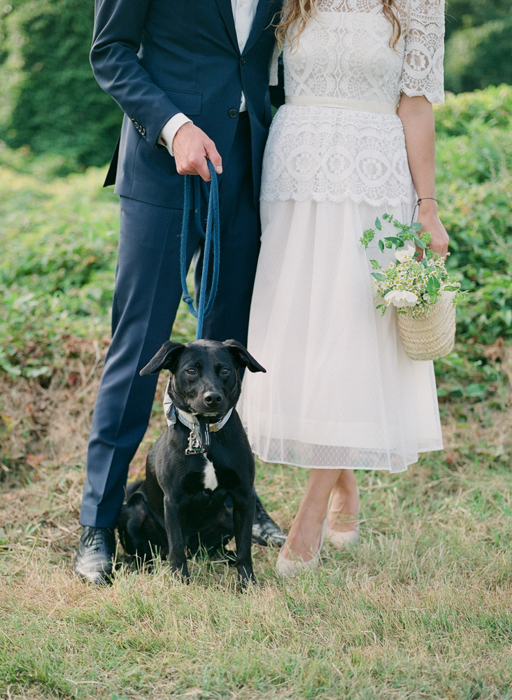 bride and groom with black dog at their feet