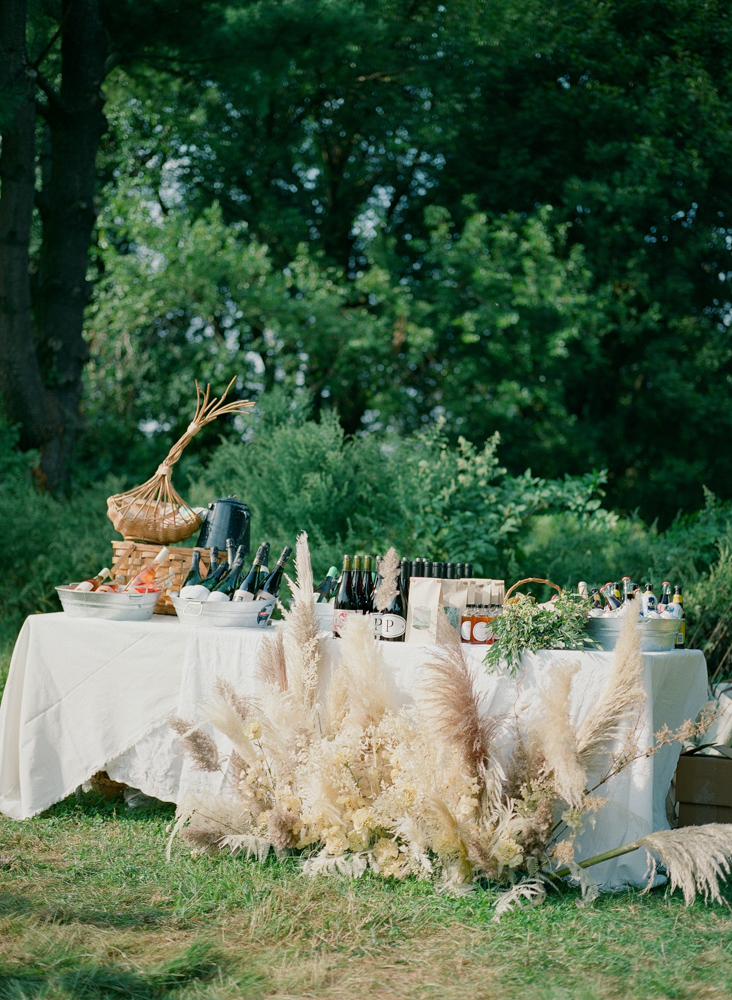 long table with wedding drinks at reception picnic