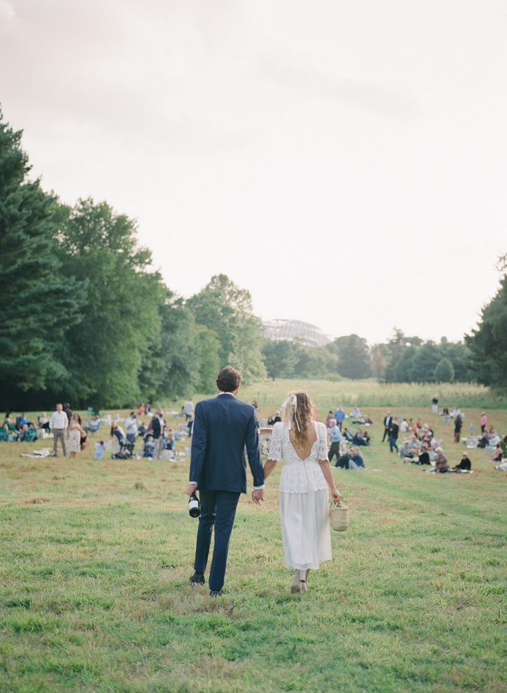 couple holding hands entering reception picnic