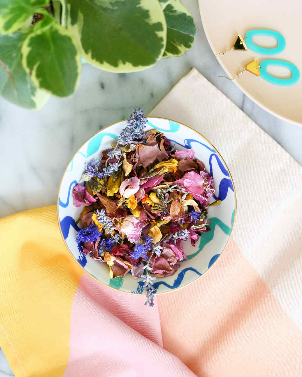 ornate bowl of potpourri with plant and earrings