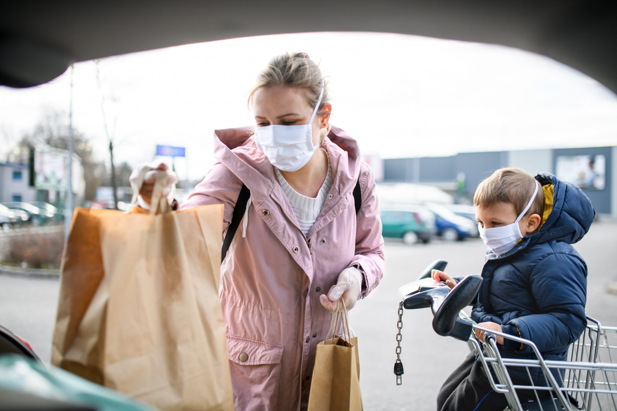 mother and small son with face mask outdoors putting shopping bags in car