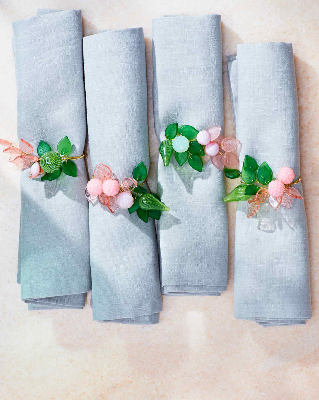 a set of napkins with floral beads cinched in the middle
