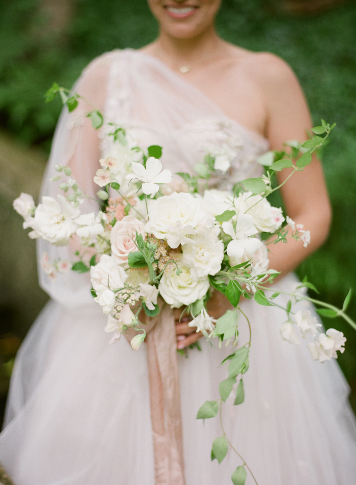 bride holding white and blush bouquet with ribbon