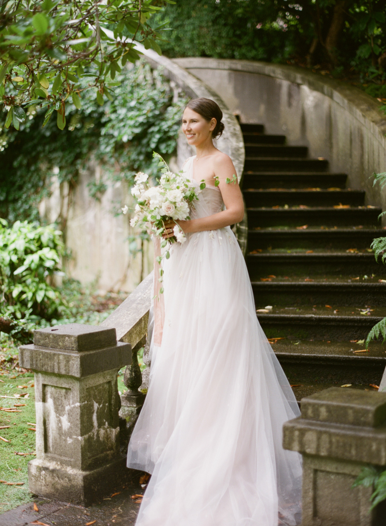 bride in flowing white tulle dress on stone stairway