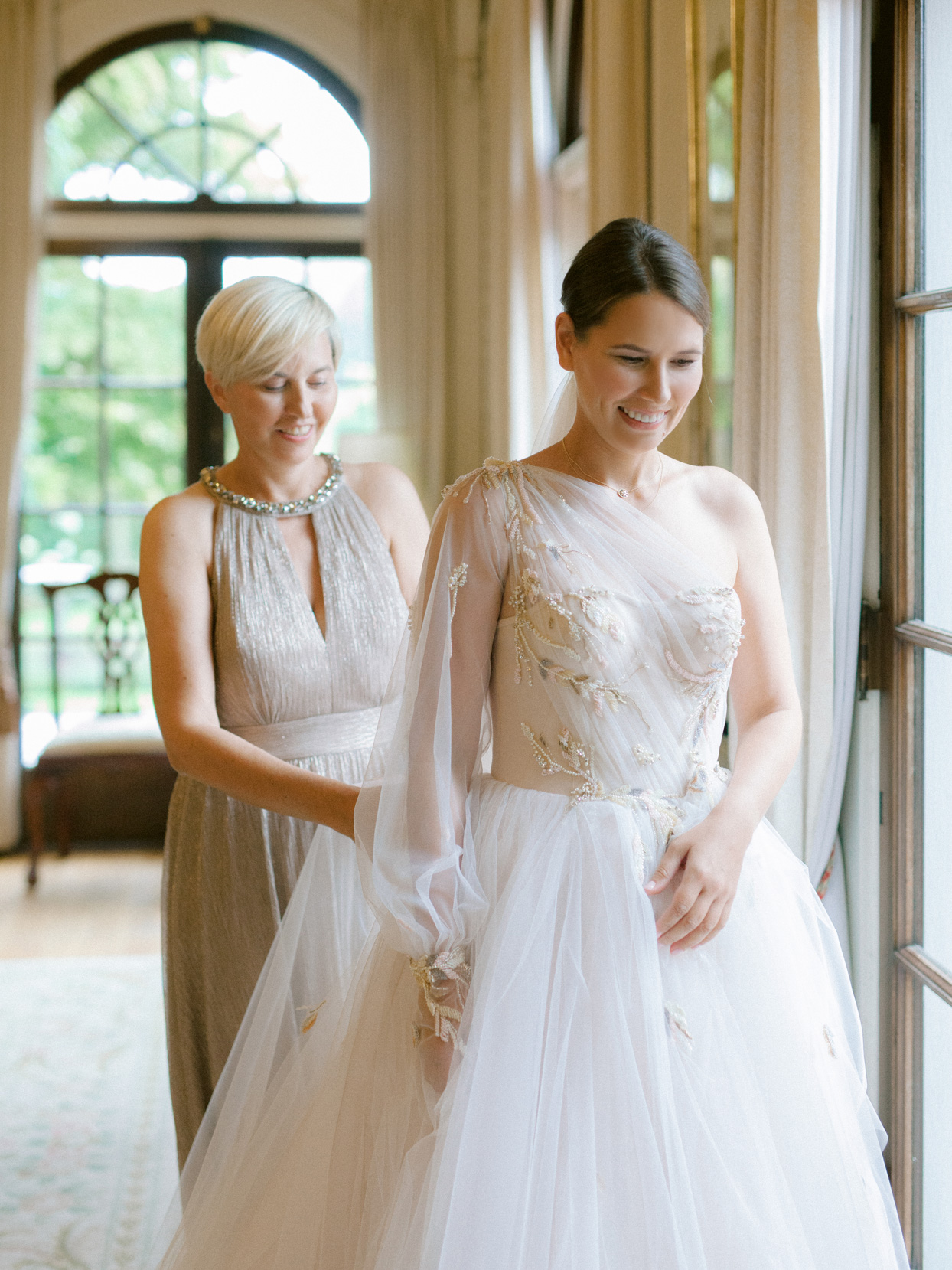mother helping bride get ready in front of large windows
