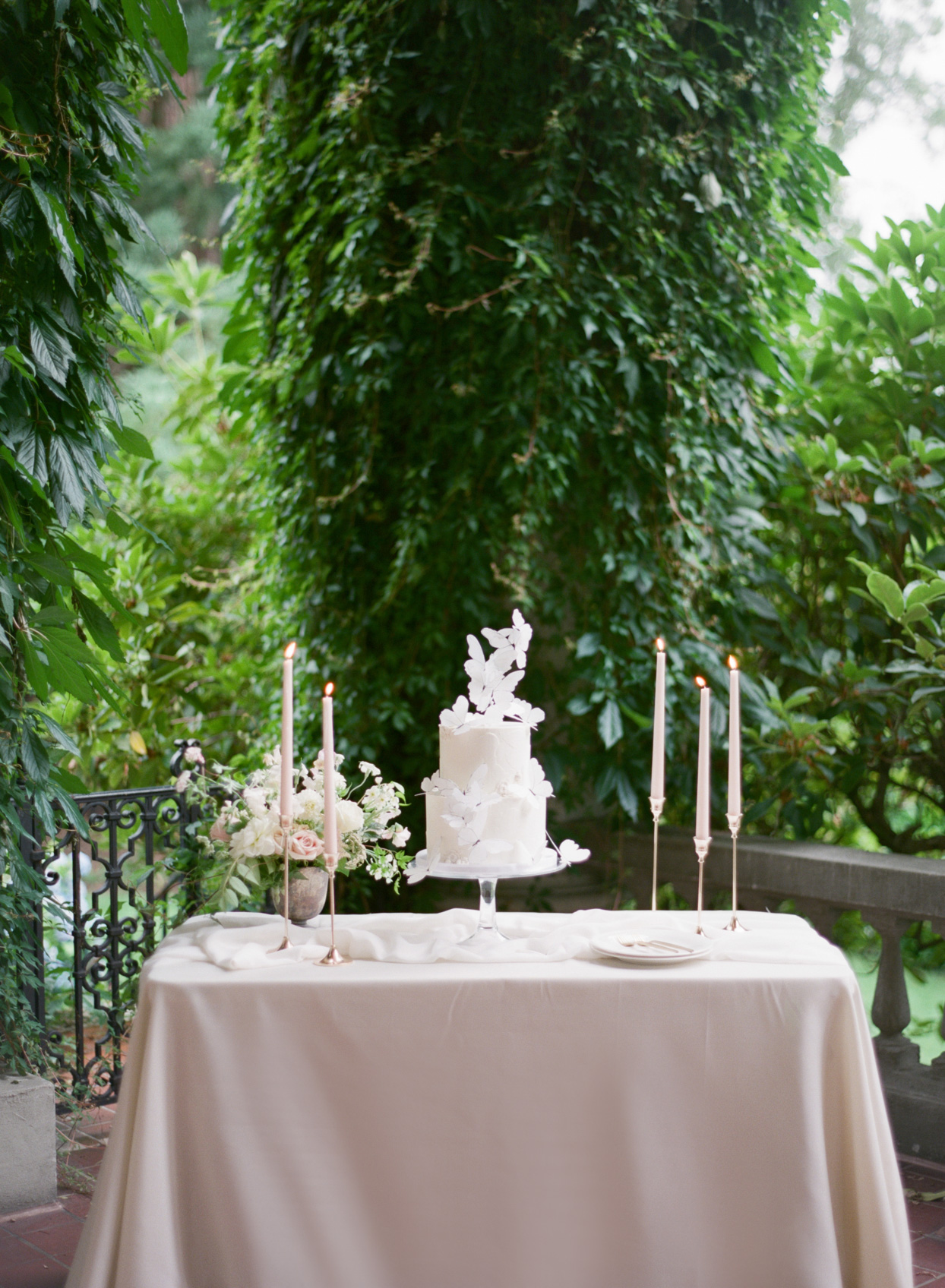 elegant wedding cake, candles, and bouquet on table
