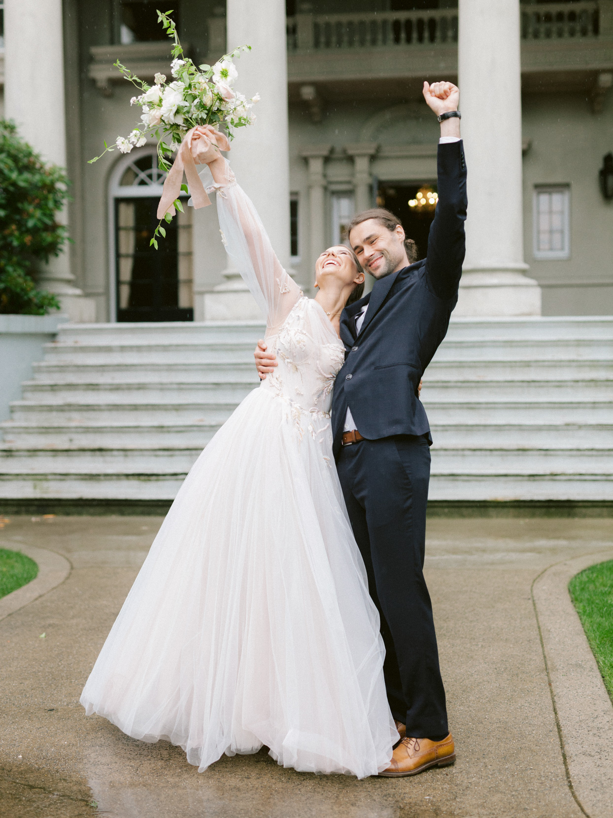 wedding couple raising hands in expression of joy