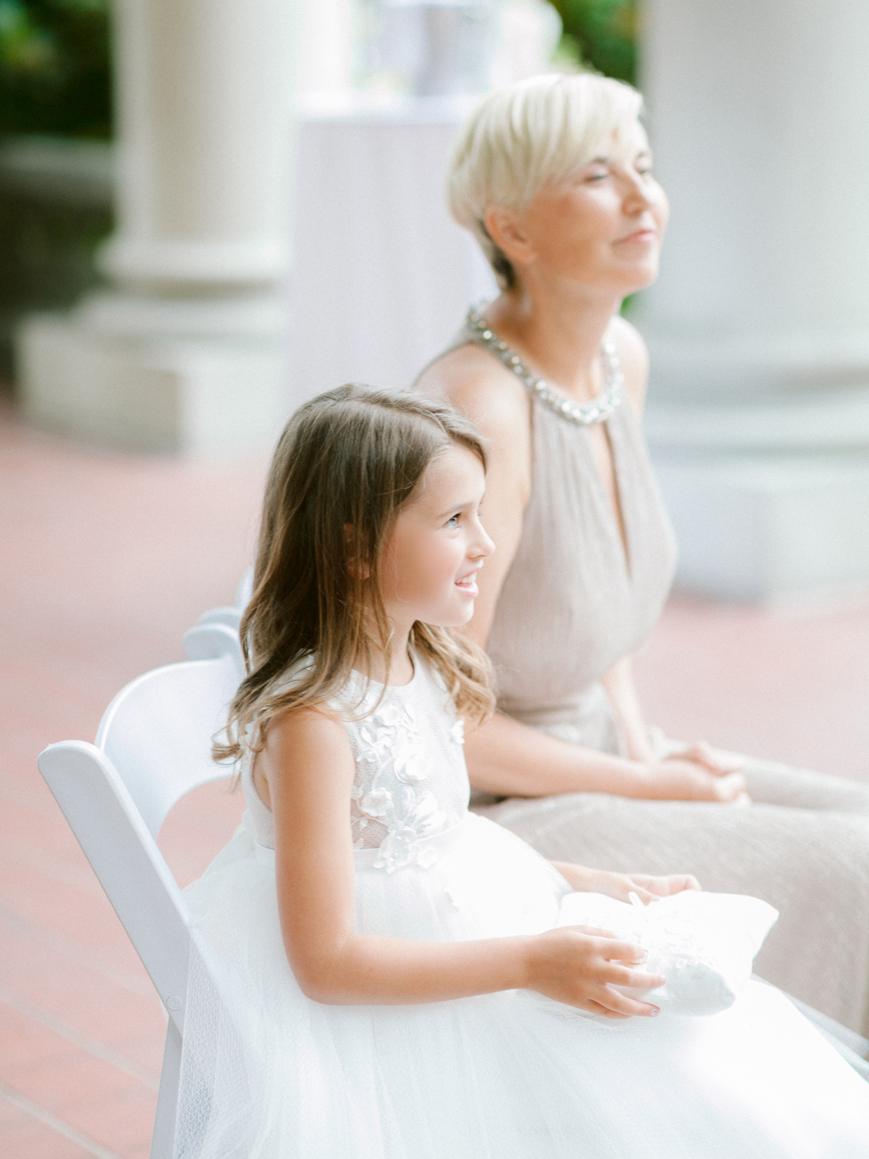 daughter sitting with mother of bride at wedding