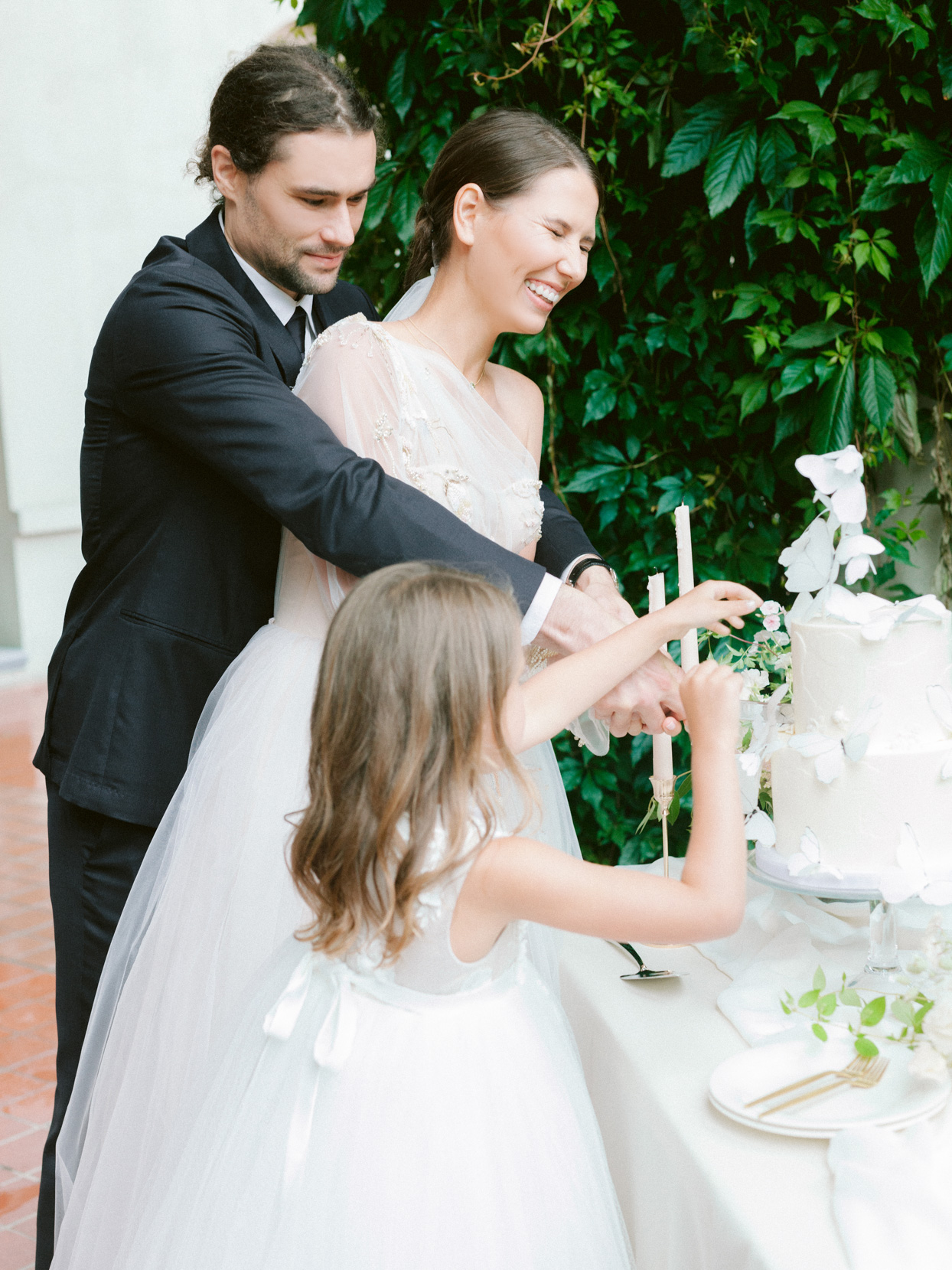 bride, groom, and daughter cutting wedding cake together