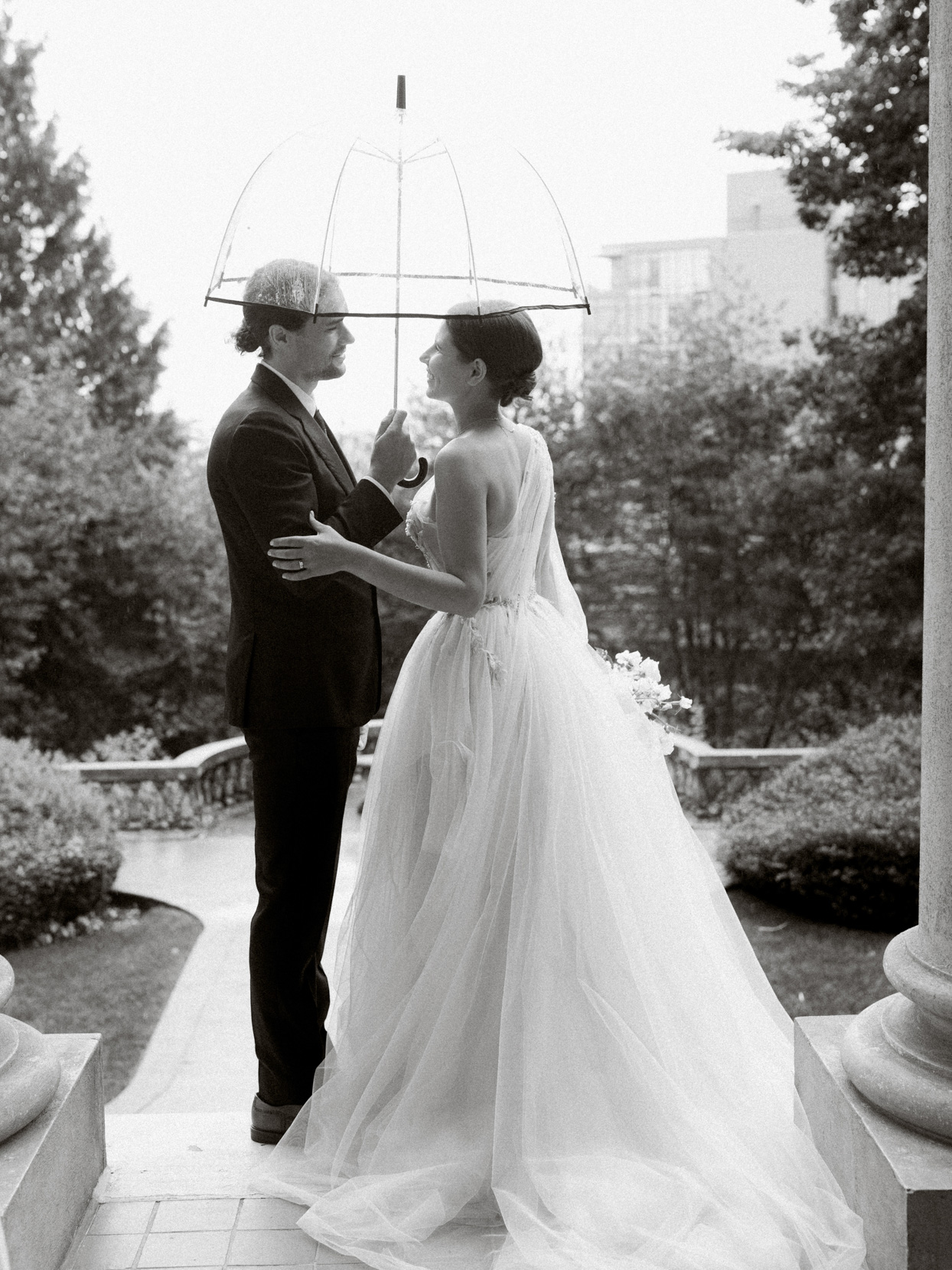 wedding couple standing on steps with clear umbrella
