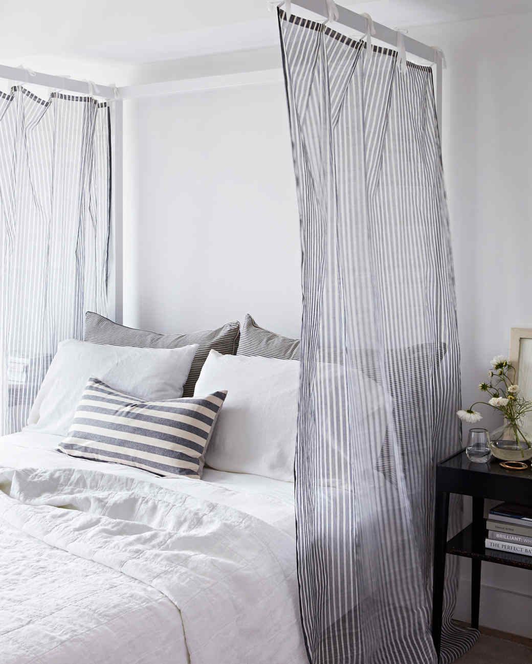 gray and white striped four-poster bed with canopy panels