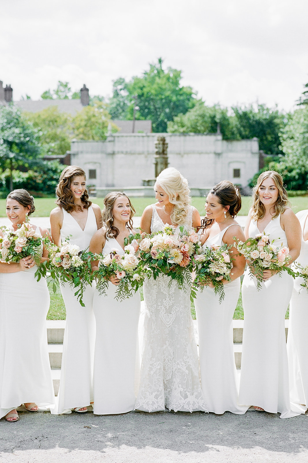 bride standing with bridesmaids wearing white dresses