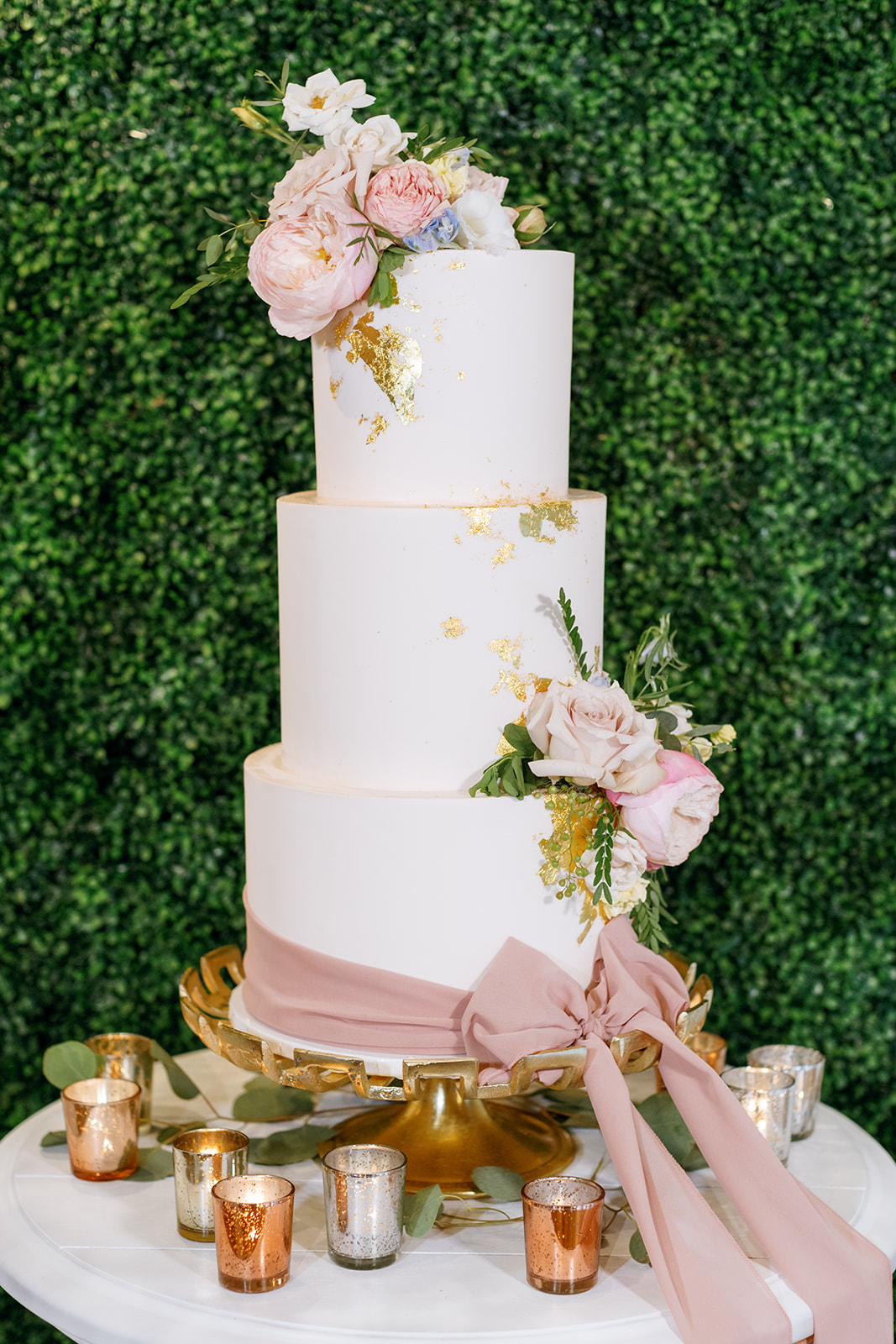 three tiered white frosted wedding cake with gold foil and pink floral accents
