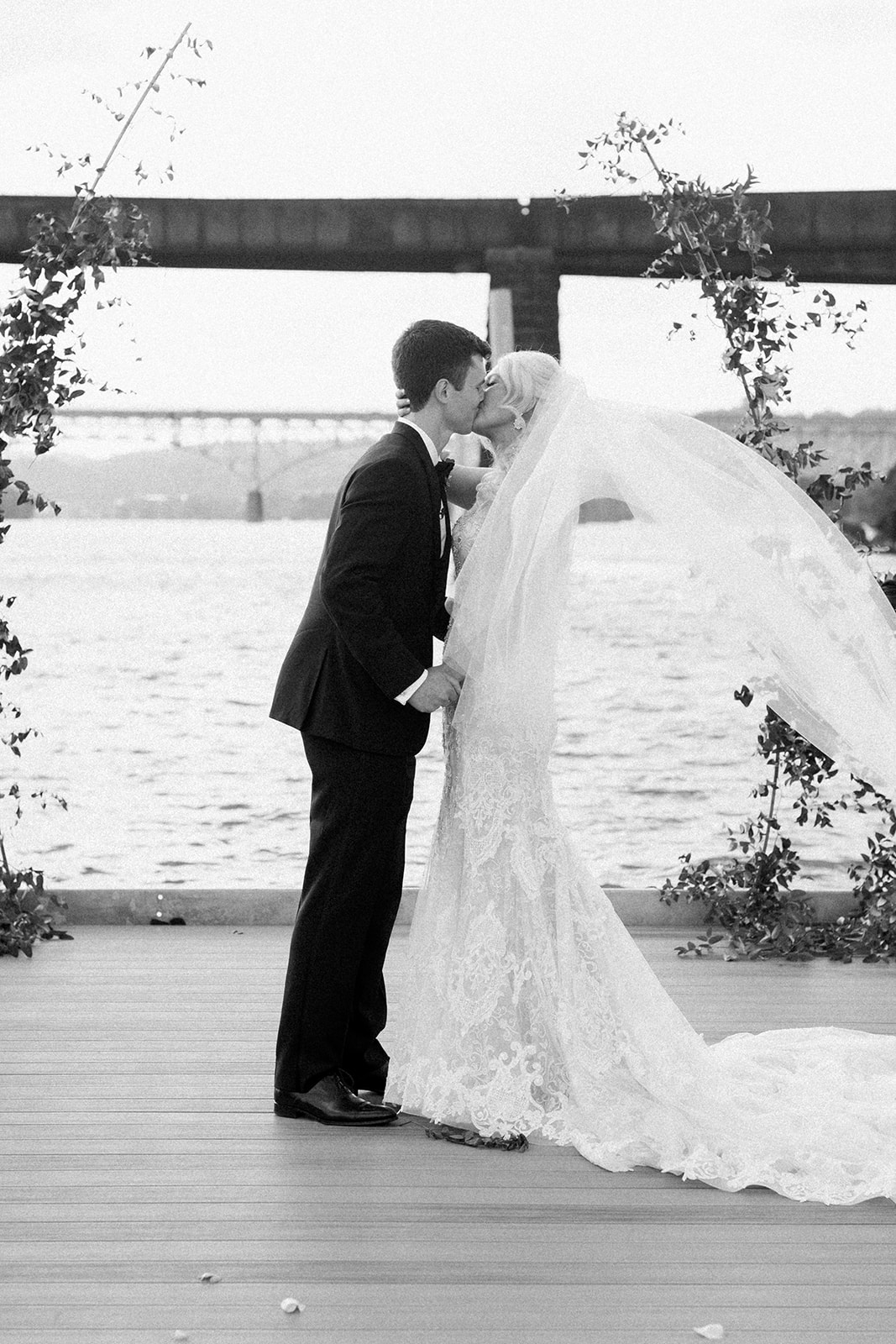 bride and groom kiss on boat doc after wedding ceremony