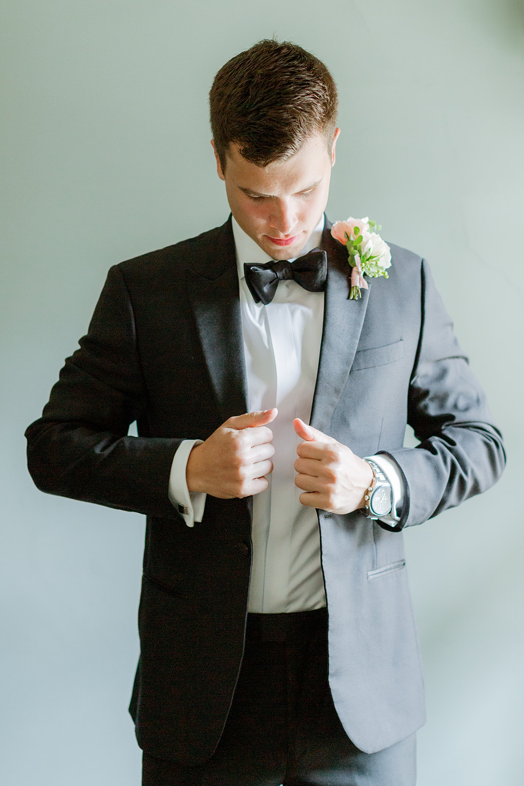 groom wearing a black tuxedo with pink floral boutonniere