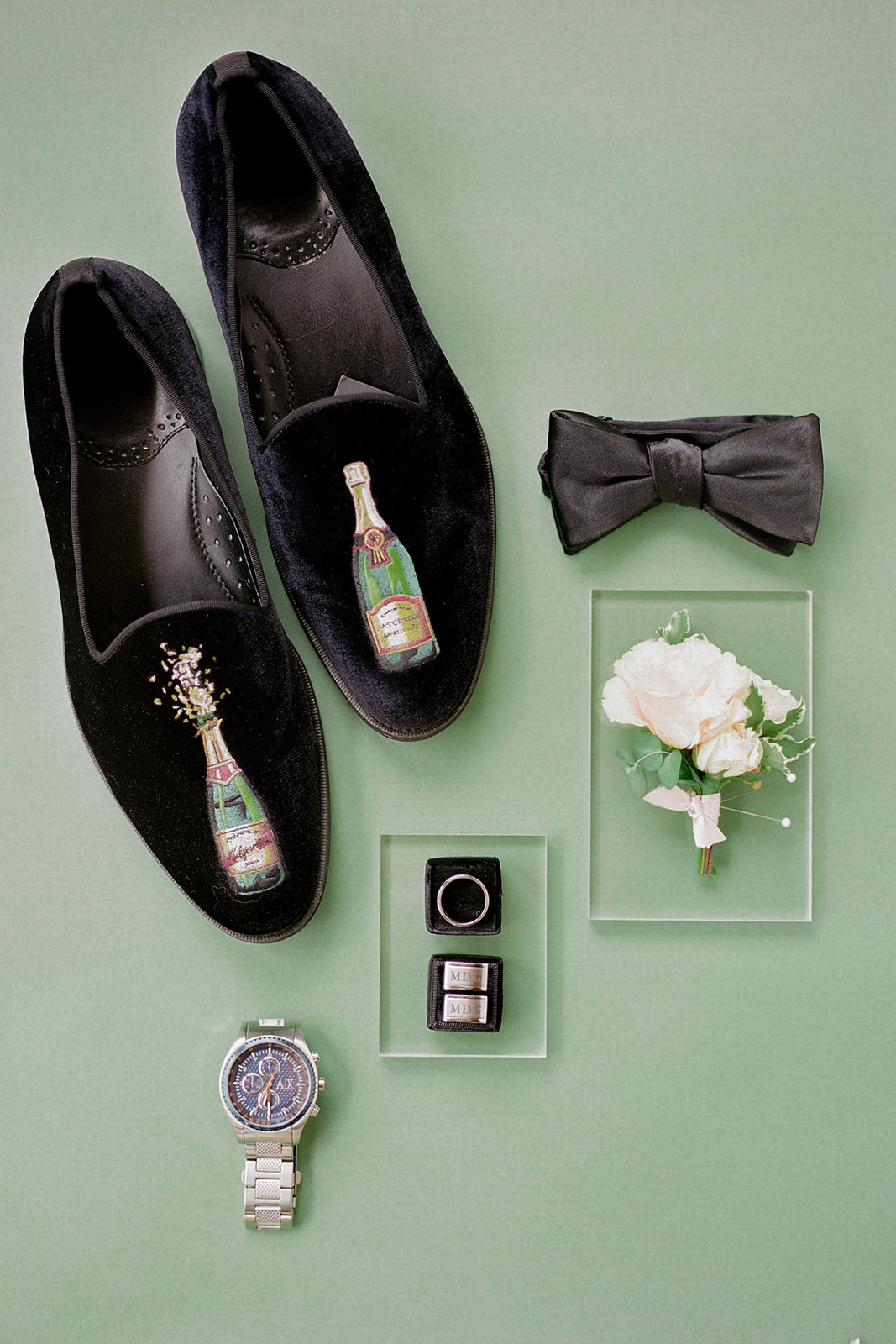 champagne bottles embroidered onto black velvet shoes with grooms accesories