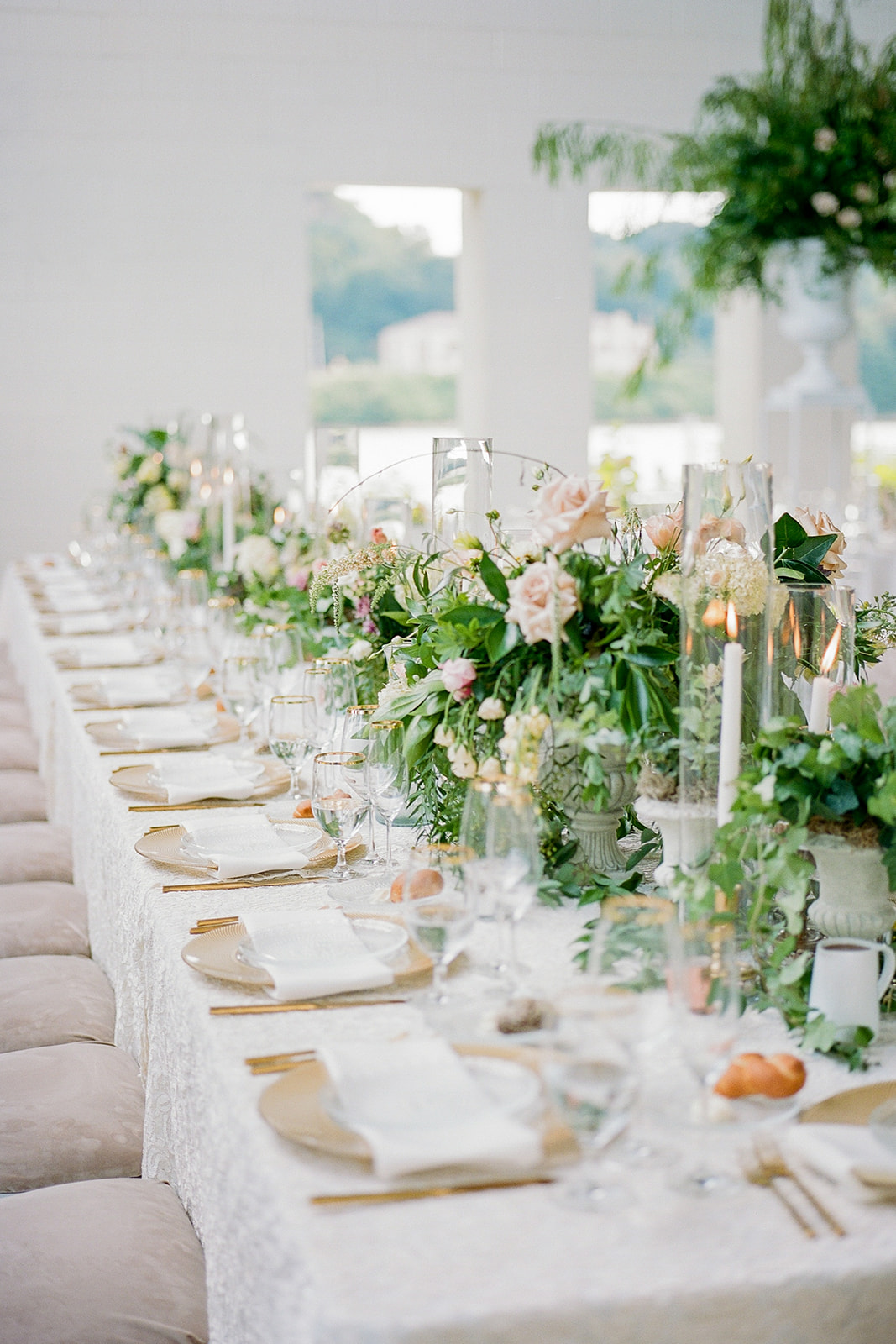 lush greenery and pink floral centerpiece lined reception tables
