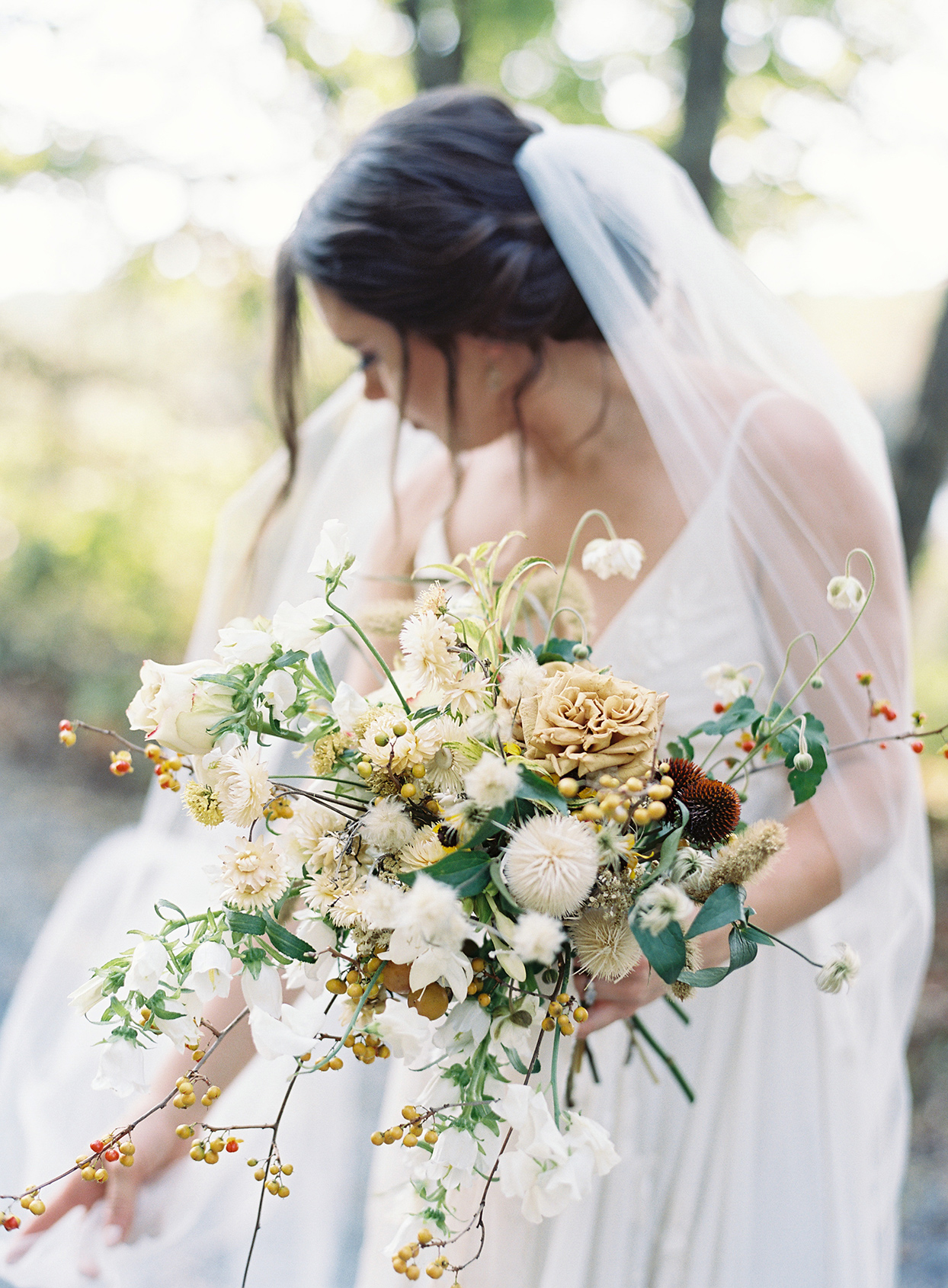 bride holding various floral and foliage rustic styled wedding bouquet