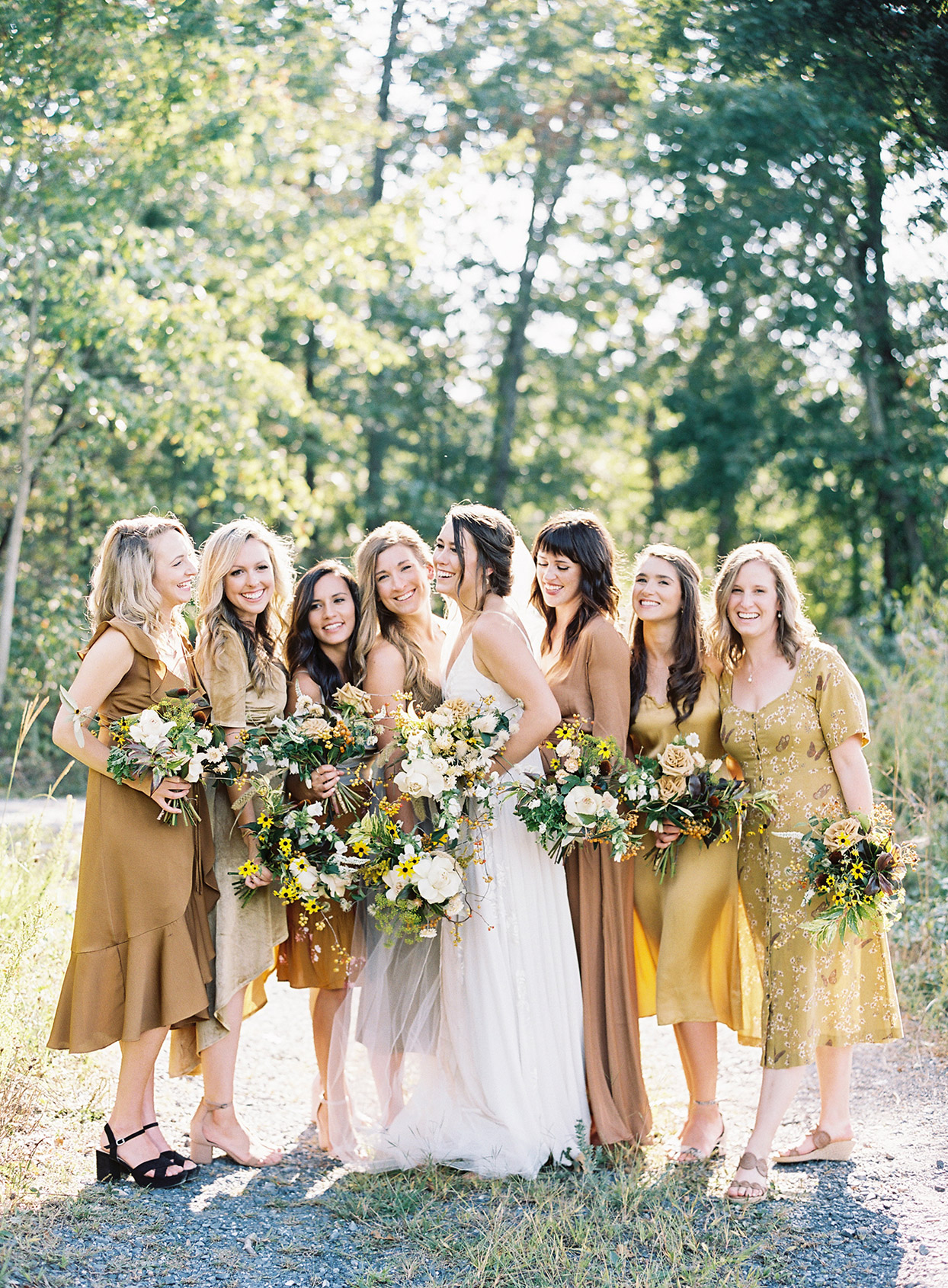 bride smiling with bridesmaids wearing various styled mustard hued dresses