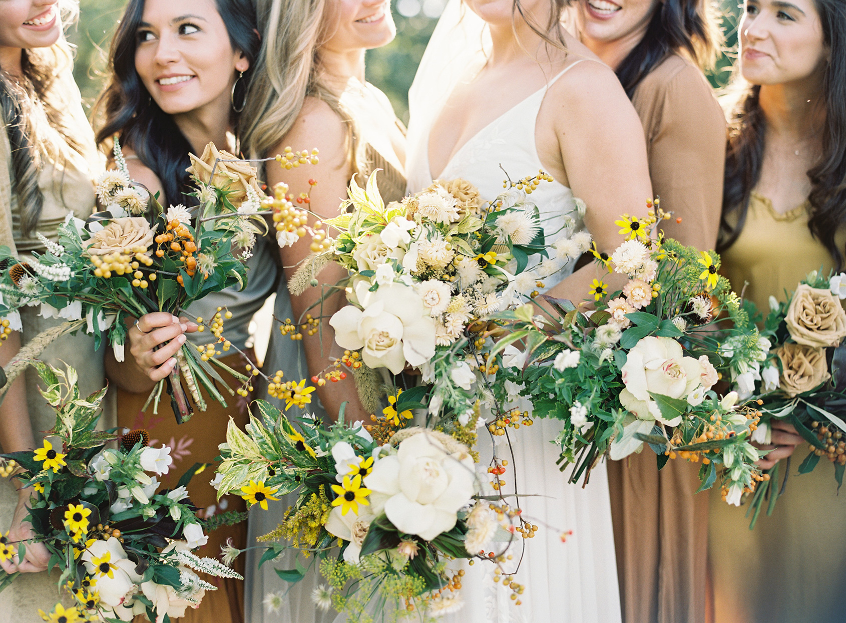 bridesmaids holding warm toned bouquets with bride