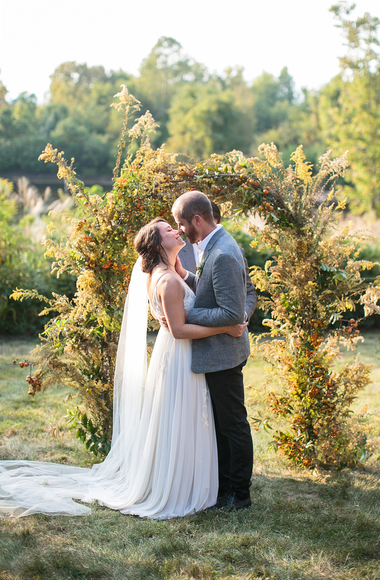 bride and groom sharing kiss next to wedding arch