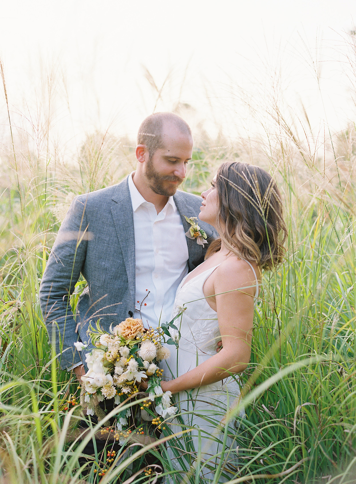bride and groom standing in tall grass outside