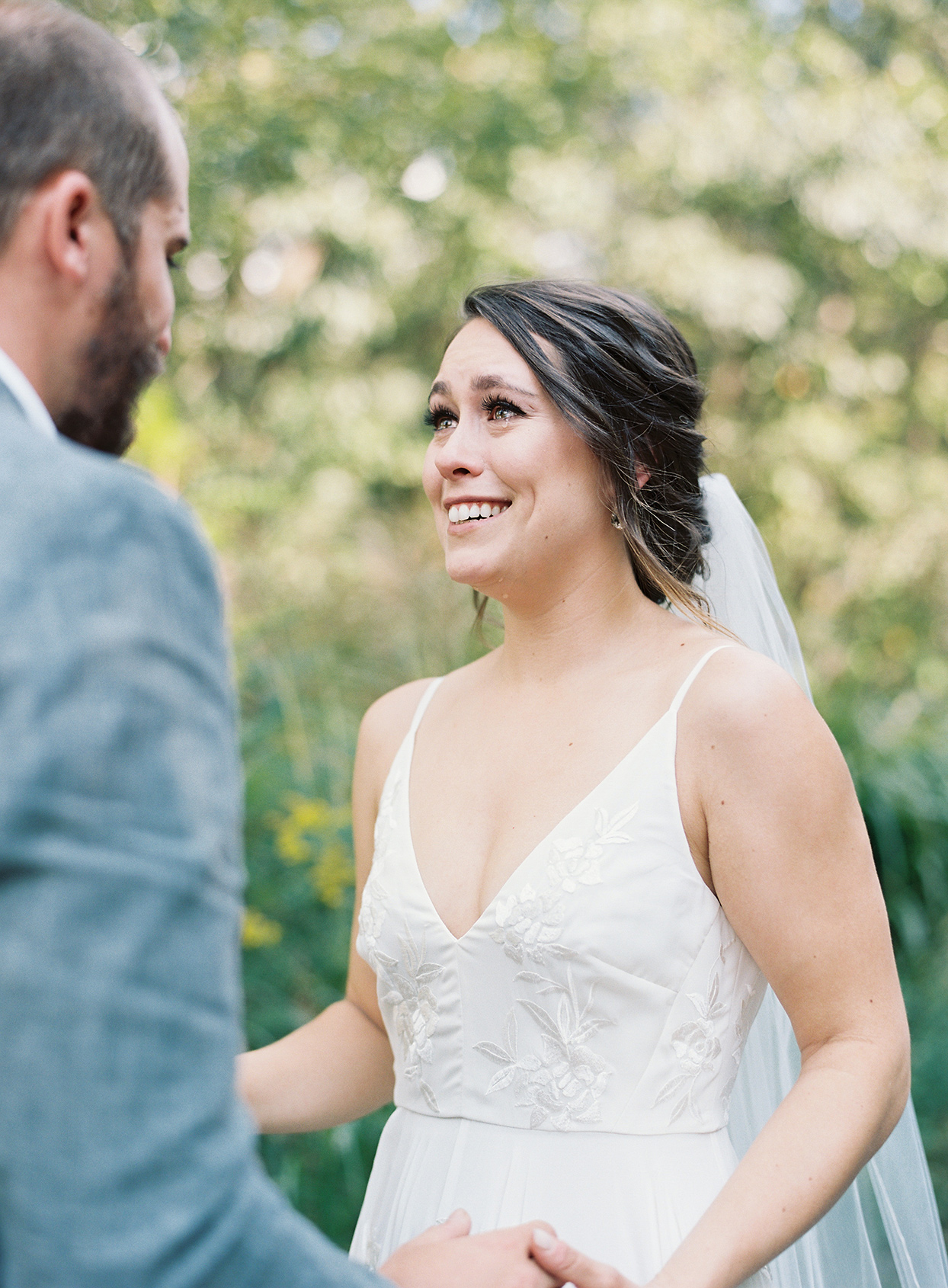 bride smiling at groom during first look outside
