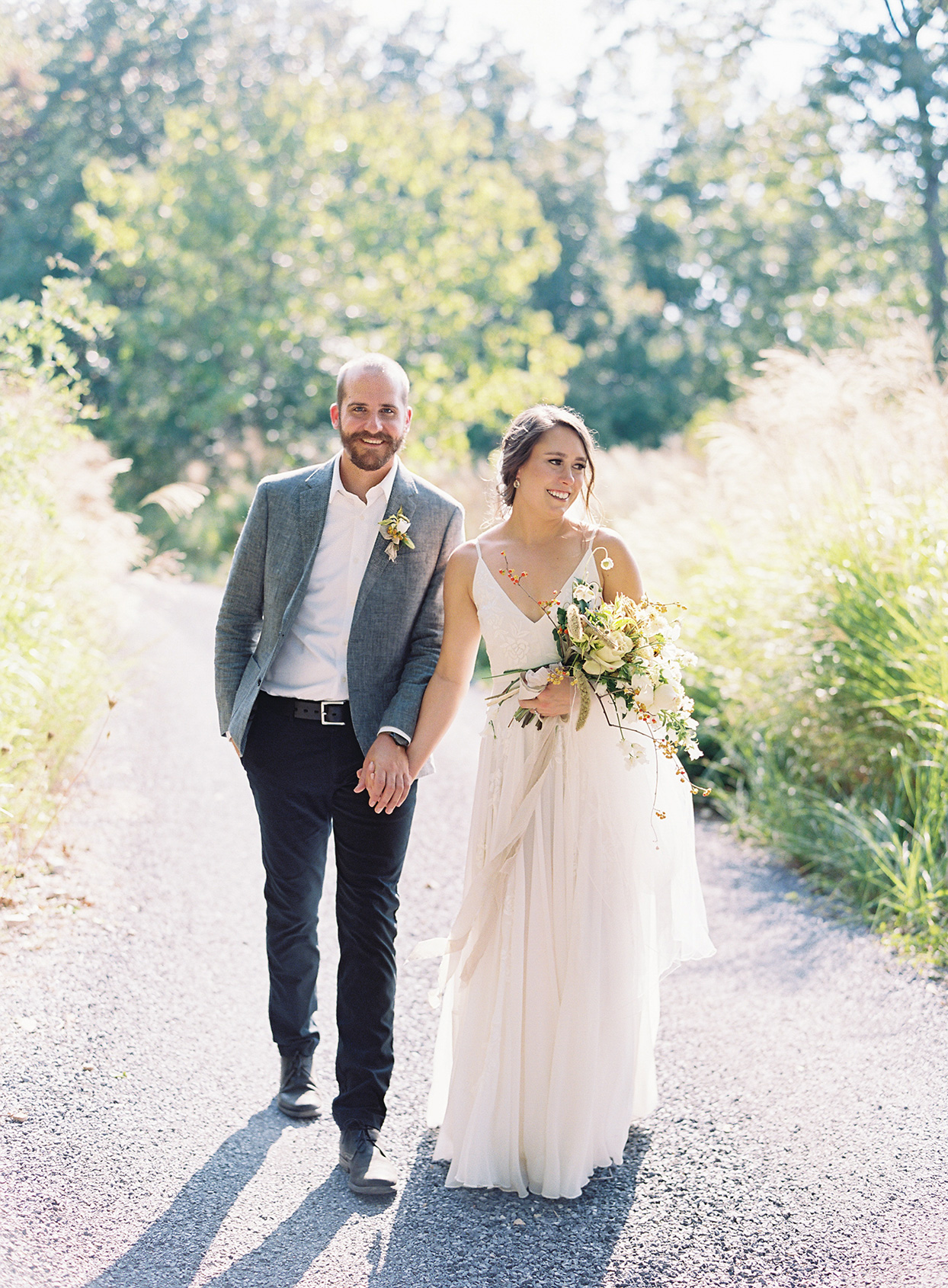 bride and groom smiling holding hands walking on gravel path