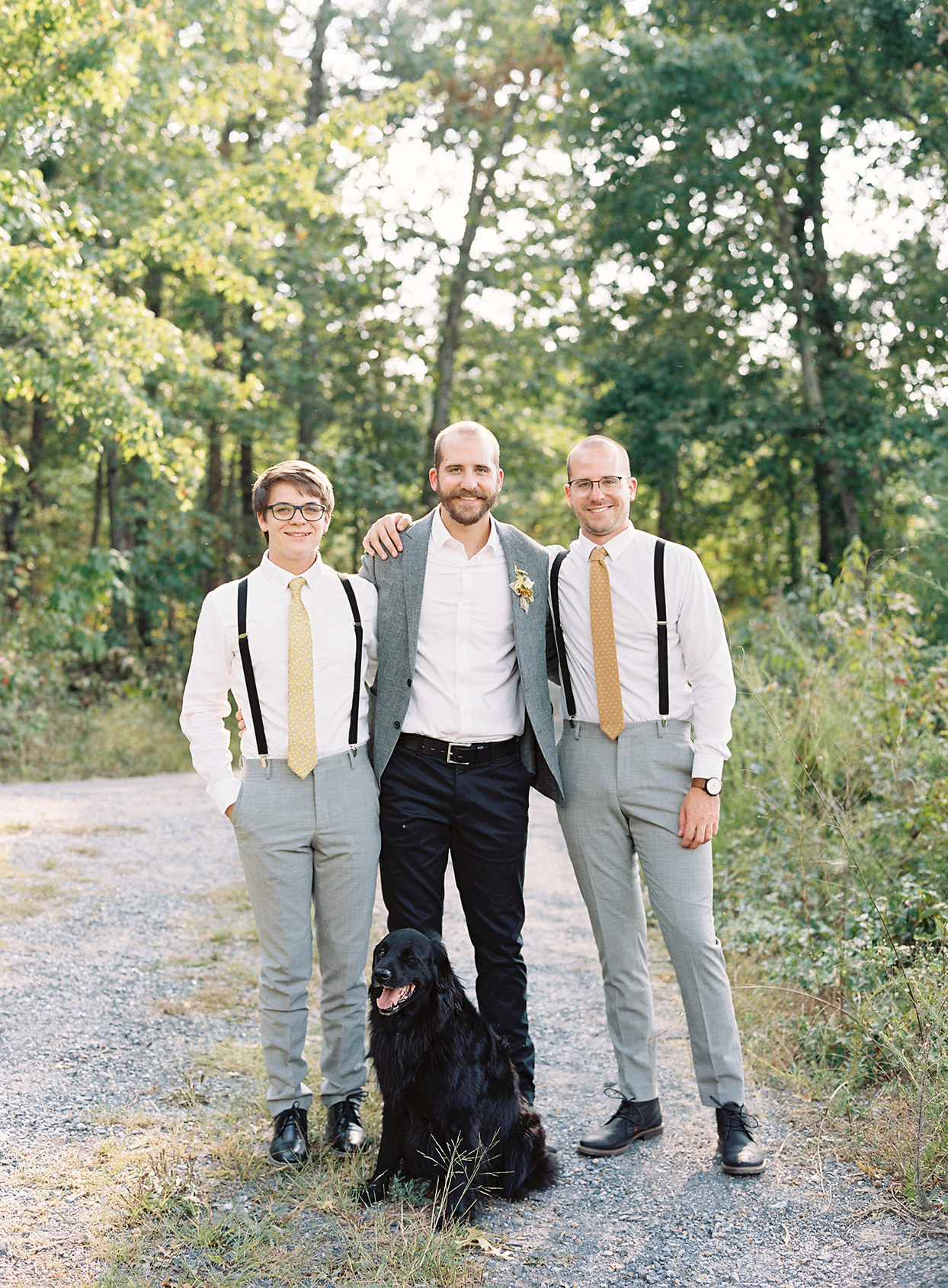 groom standing with two groomsmen and dog