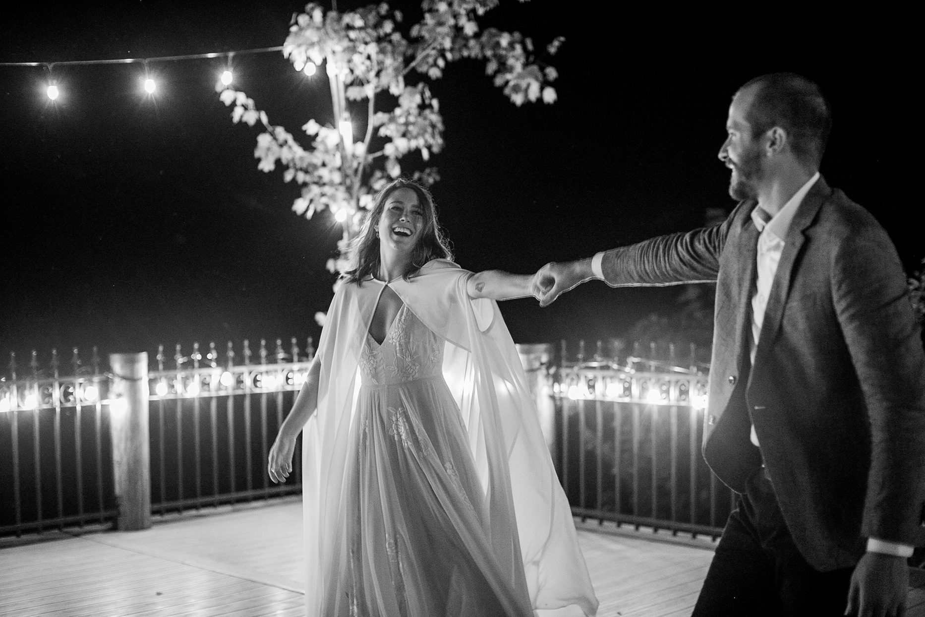 bride and groom smiling holding hands during first dance
