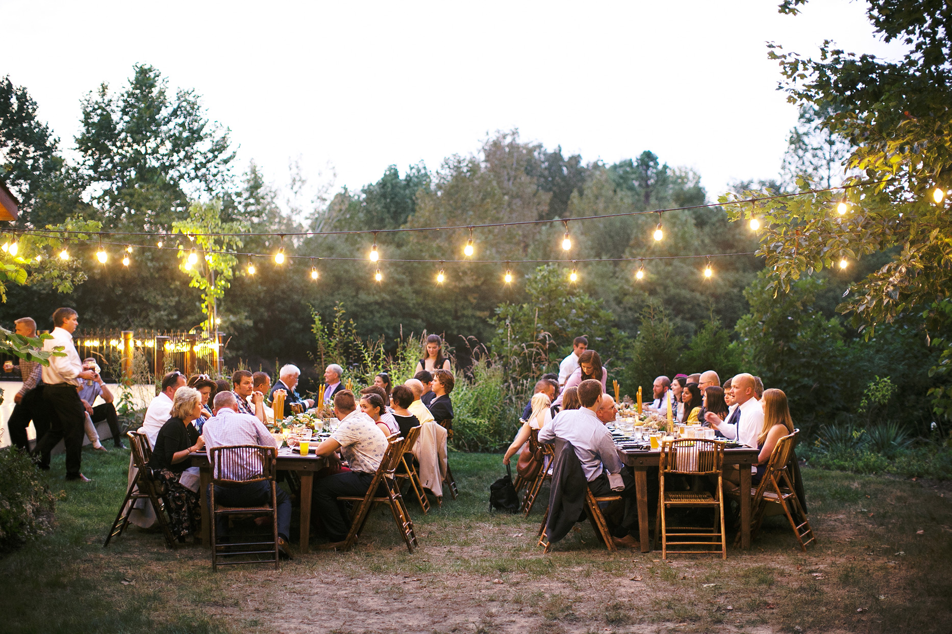 wedding reception guests seated under string lighting