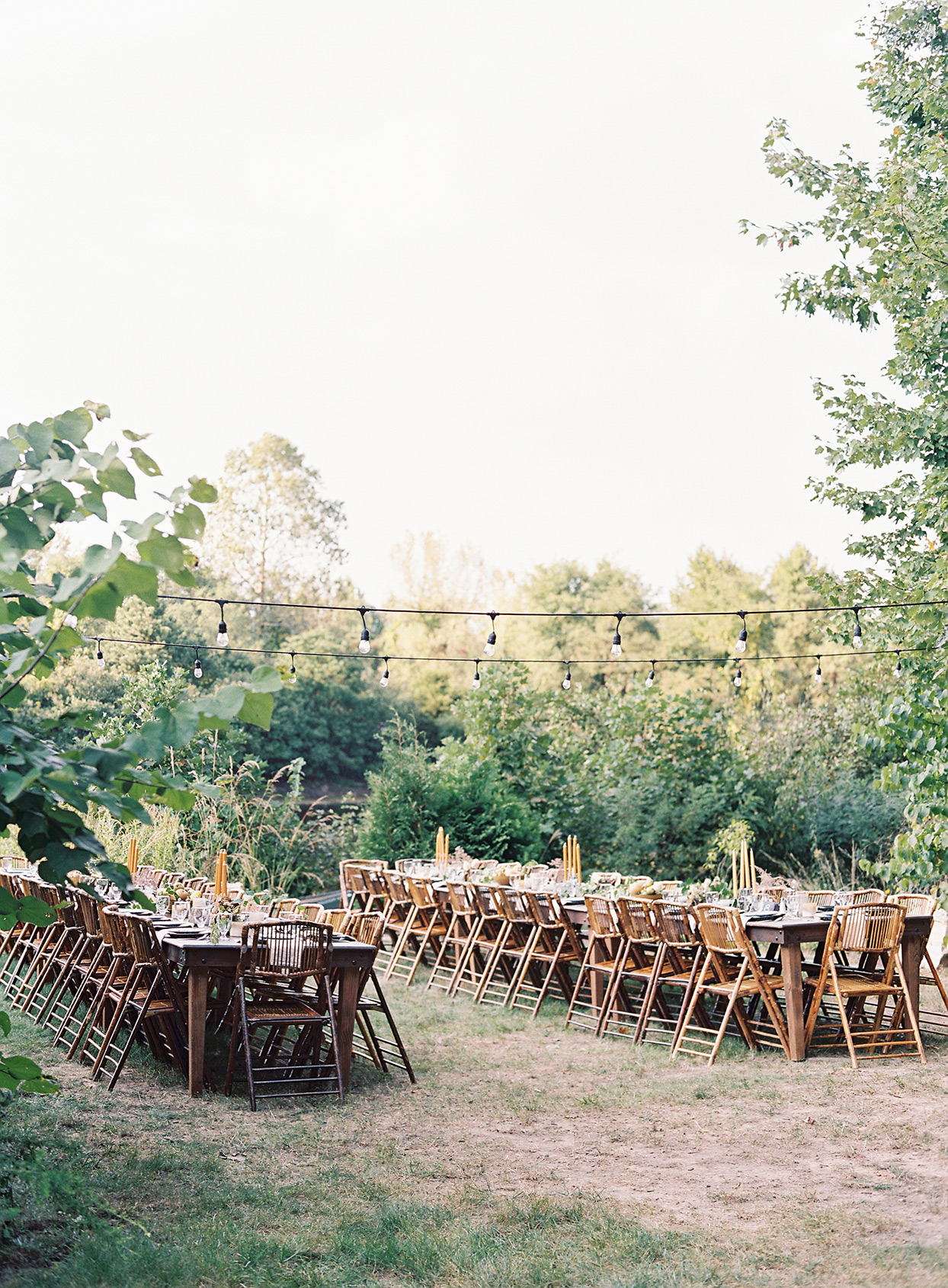 long wooden tables lined with matching chairs under string lights