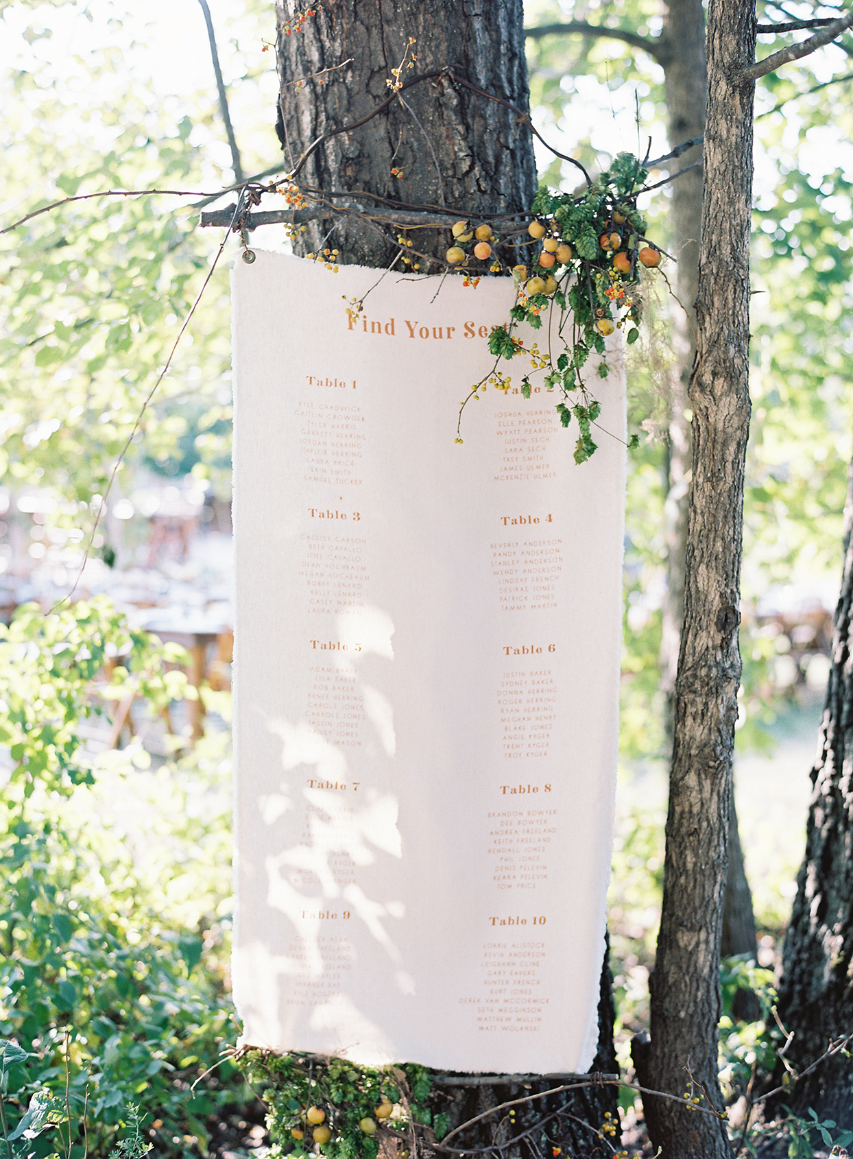 raw edge linen seating chart hanging on tree