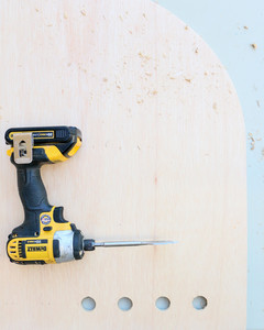power drill atop birch plywood with holes