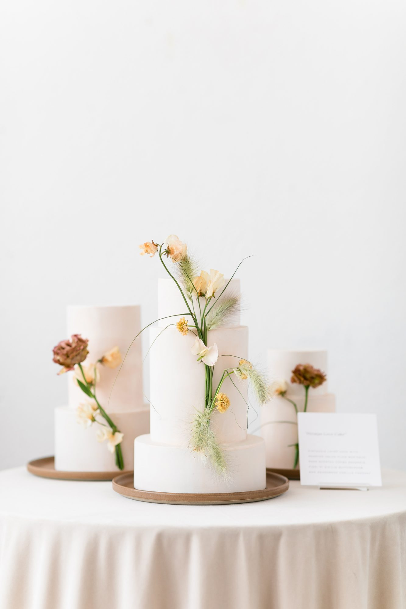 three smooth white multi-tiered wedding cakes embellished with flowers
